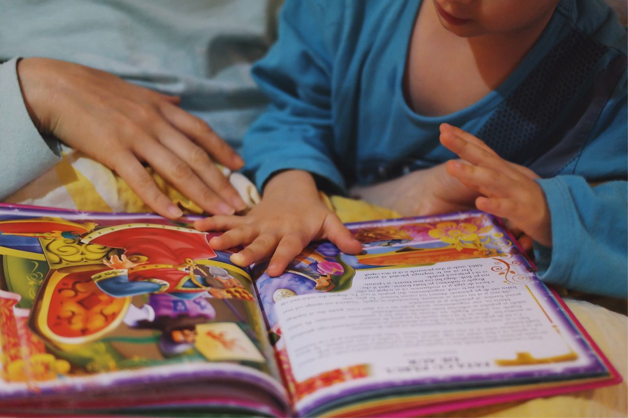 real people, book, childhood, indoors, learning, education, human hand, midsection, togetherness, leisure activity, lifestyles, two people, boys, domestic life, playing, sitting, bed, child, close-up, human body part, day, people