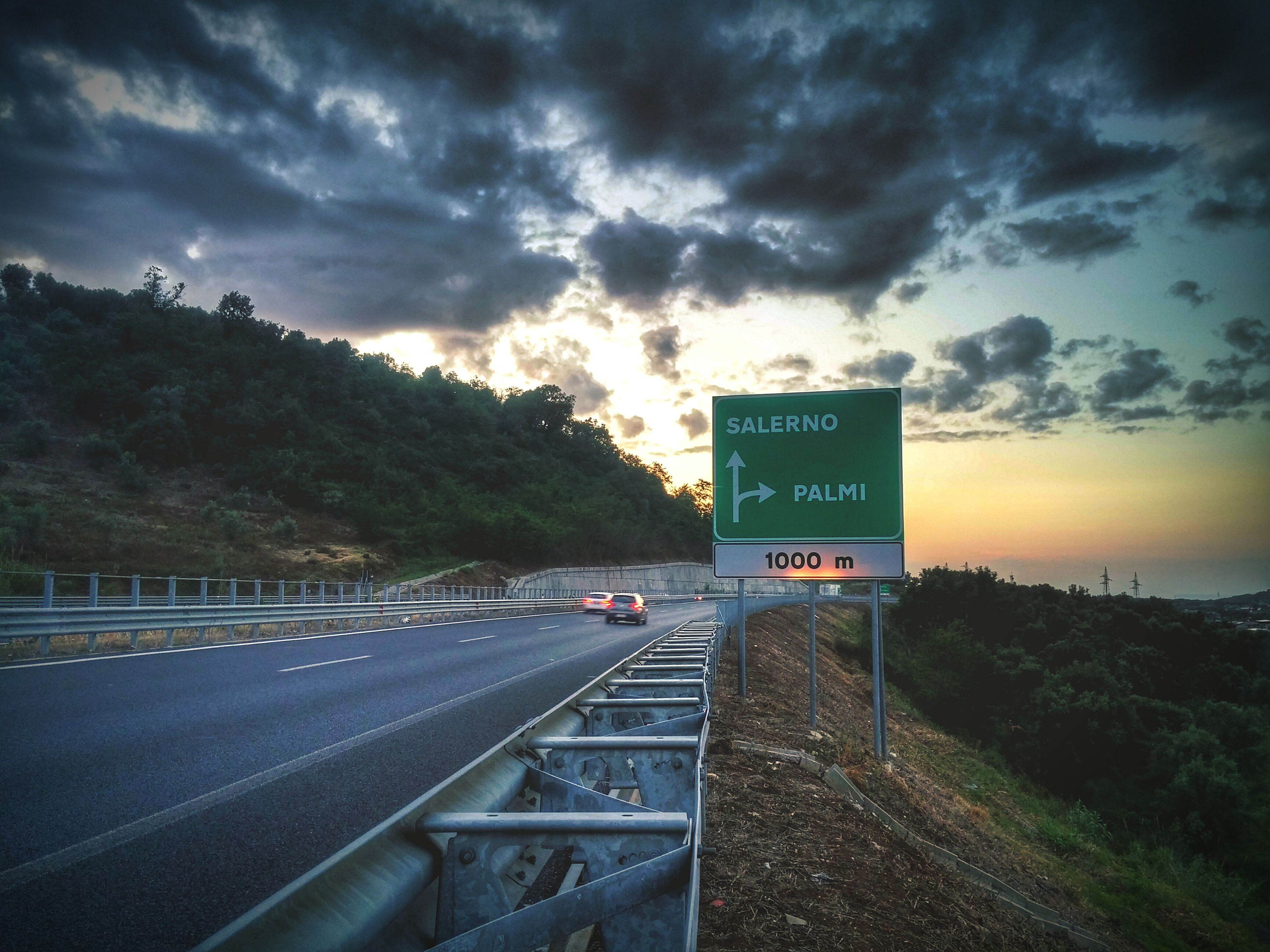 road, cloud - sky, text, communication, sky, transportation, the way forward, guidance, dramatic sky, road sign, tree, direction, sunset, travel, outdoors, no people, storm cloud, mountain, day, nature