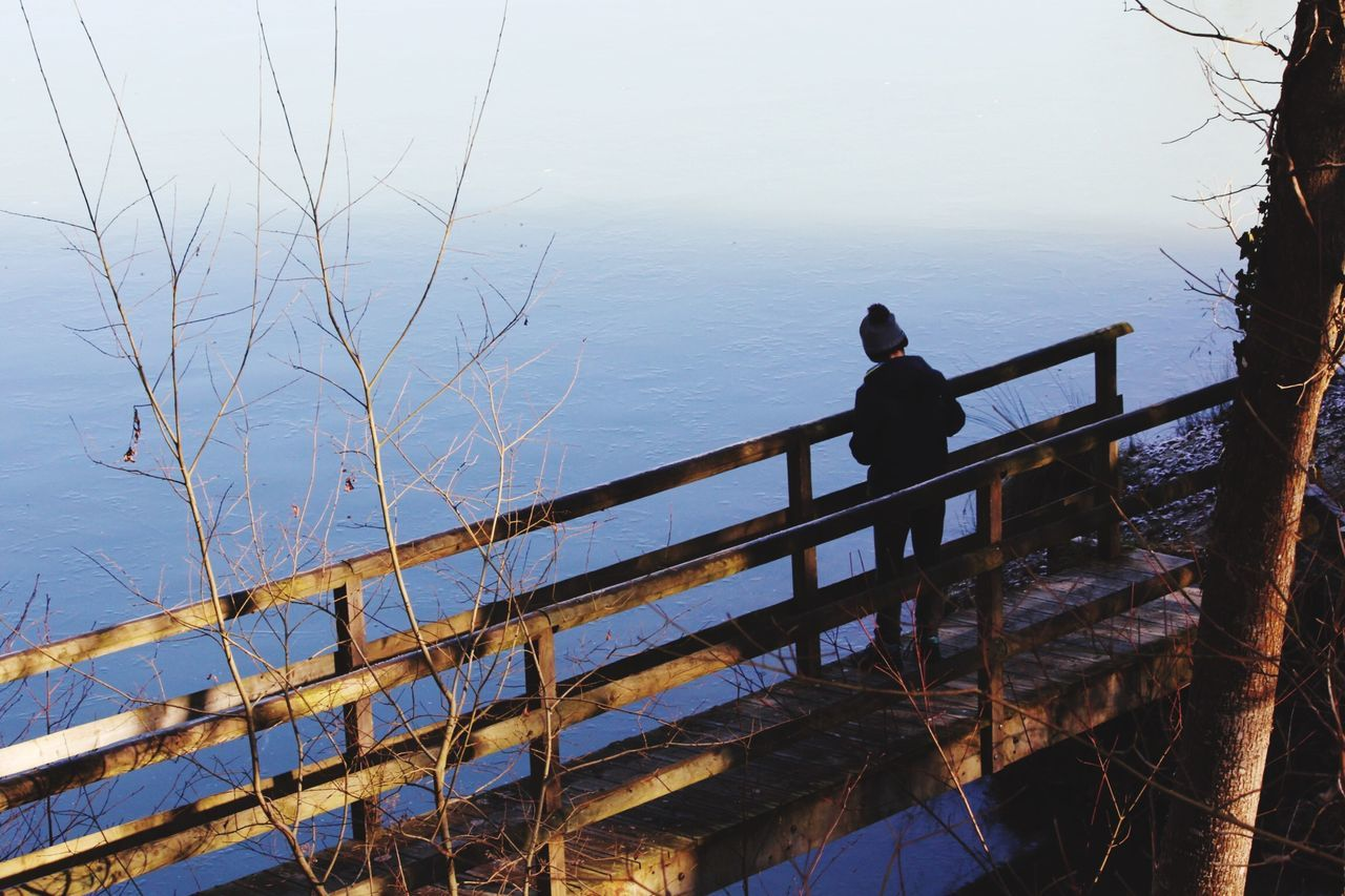 railing, water, nature, one person, sea, day, real people, tranquility, beauty in nature, outdoors, scenics, sitting, tree, sky, people