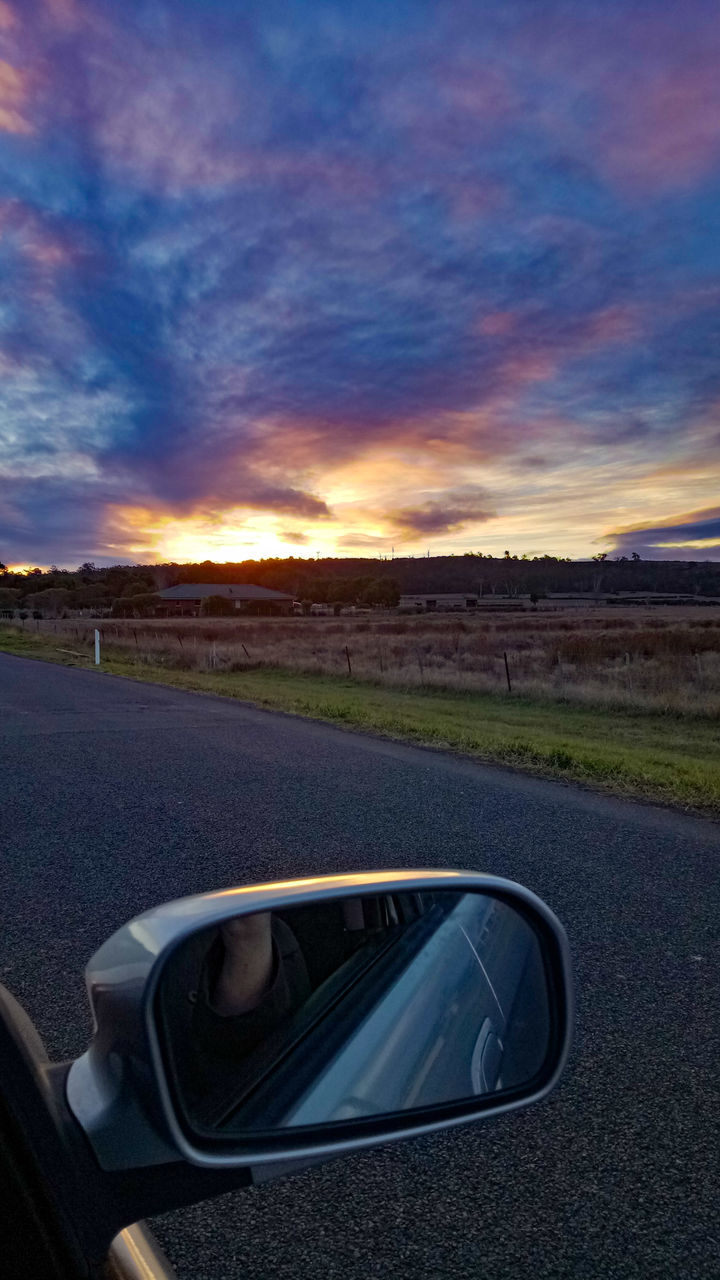 road, car, mirror, transportation, side-view mirror, sunset, cloud - sky, reflection, land vehicle, road trip, landscape, sky, vehicle mirror, outdoors, nature, no people, grass, beauty in nature, day