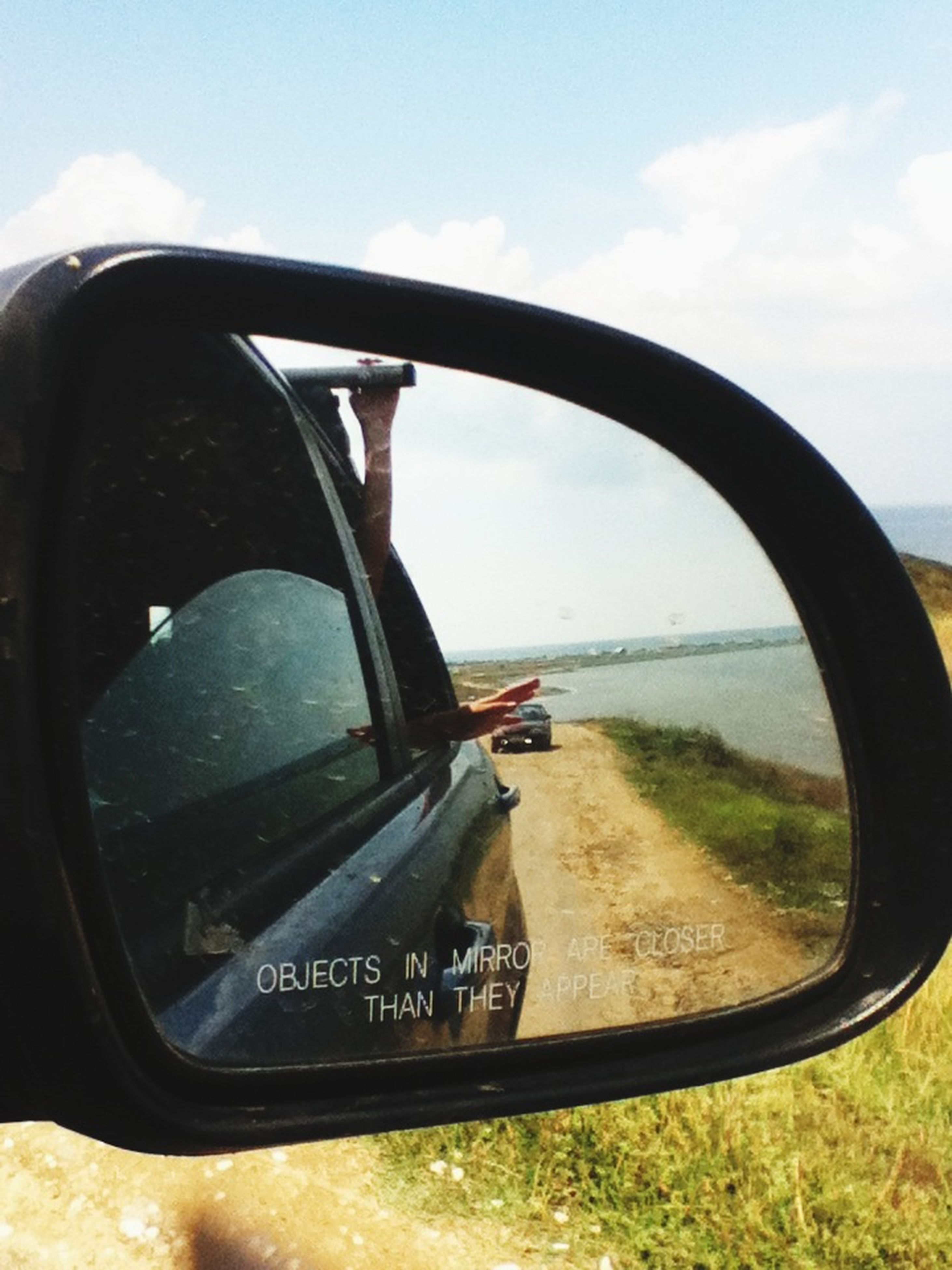 transportation, mode of transport, land vehicle, car, side-view mirror, vehicle interior, sky, car interior, glass - material, part of, road, reflection, cropped, travel, close-up, transparent, windshield, cloud - sky, vehicle part, cloud