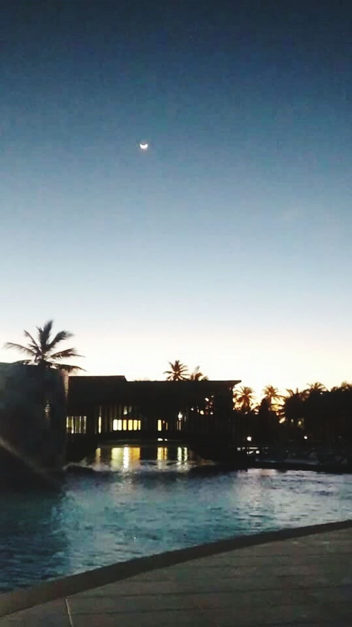 water, moon, tranquil scene, night, built structure, silhouette, scenics, sky, sea, clear sky, outdoors, no people, architecture, tranquility, nature, beauty in nature, building exterior, illuminated
