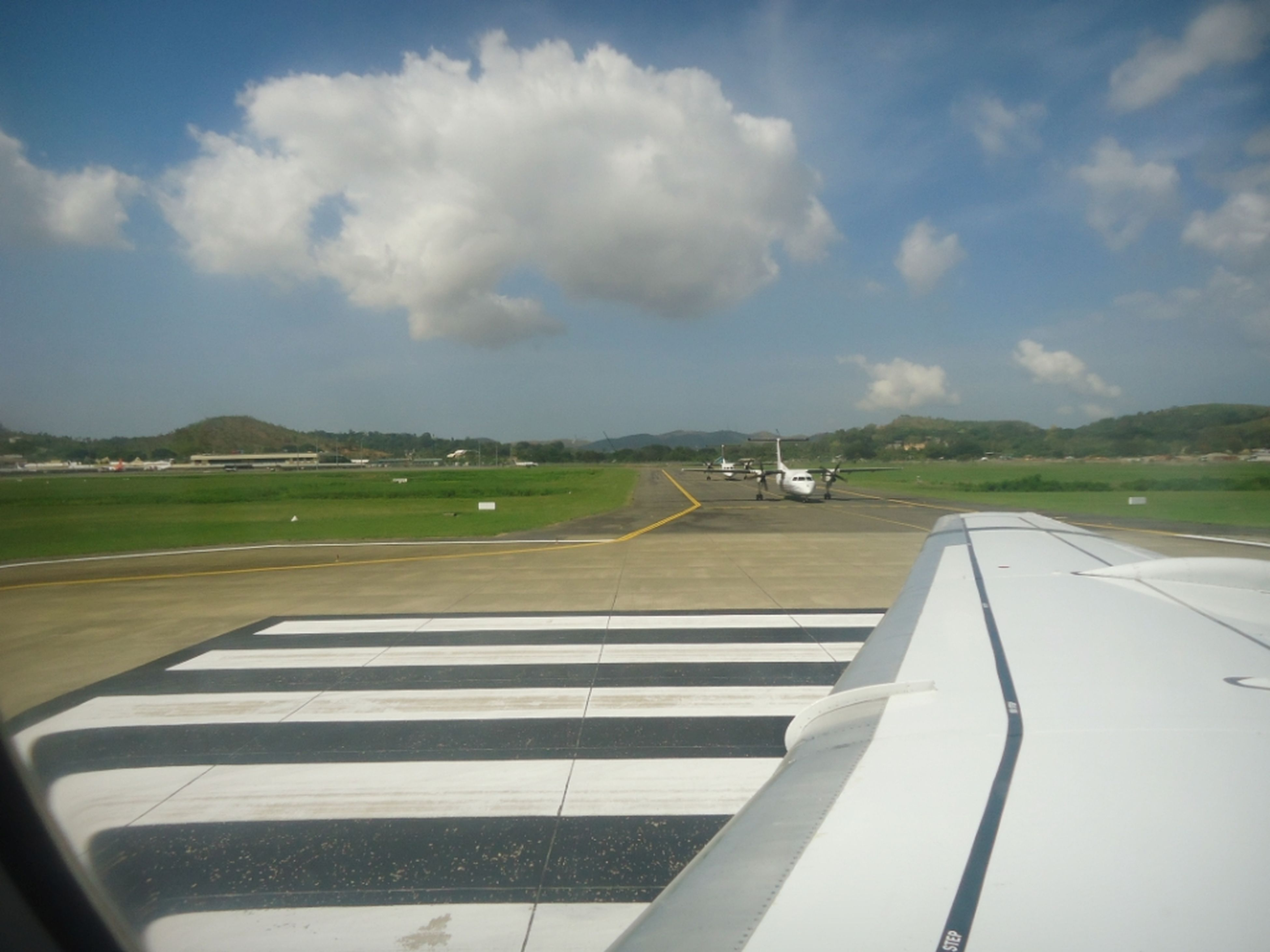 transportation, mode of transport, sky, airplane, air vehicle, cloud - sky, road marking, road, cloud, on the move, flying, cloudy, part of, travel, car, aircraft wing, cropped, airport runway, landscape, glass - material