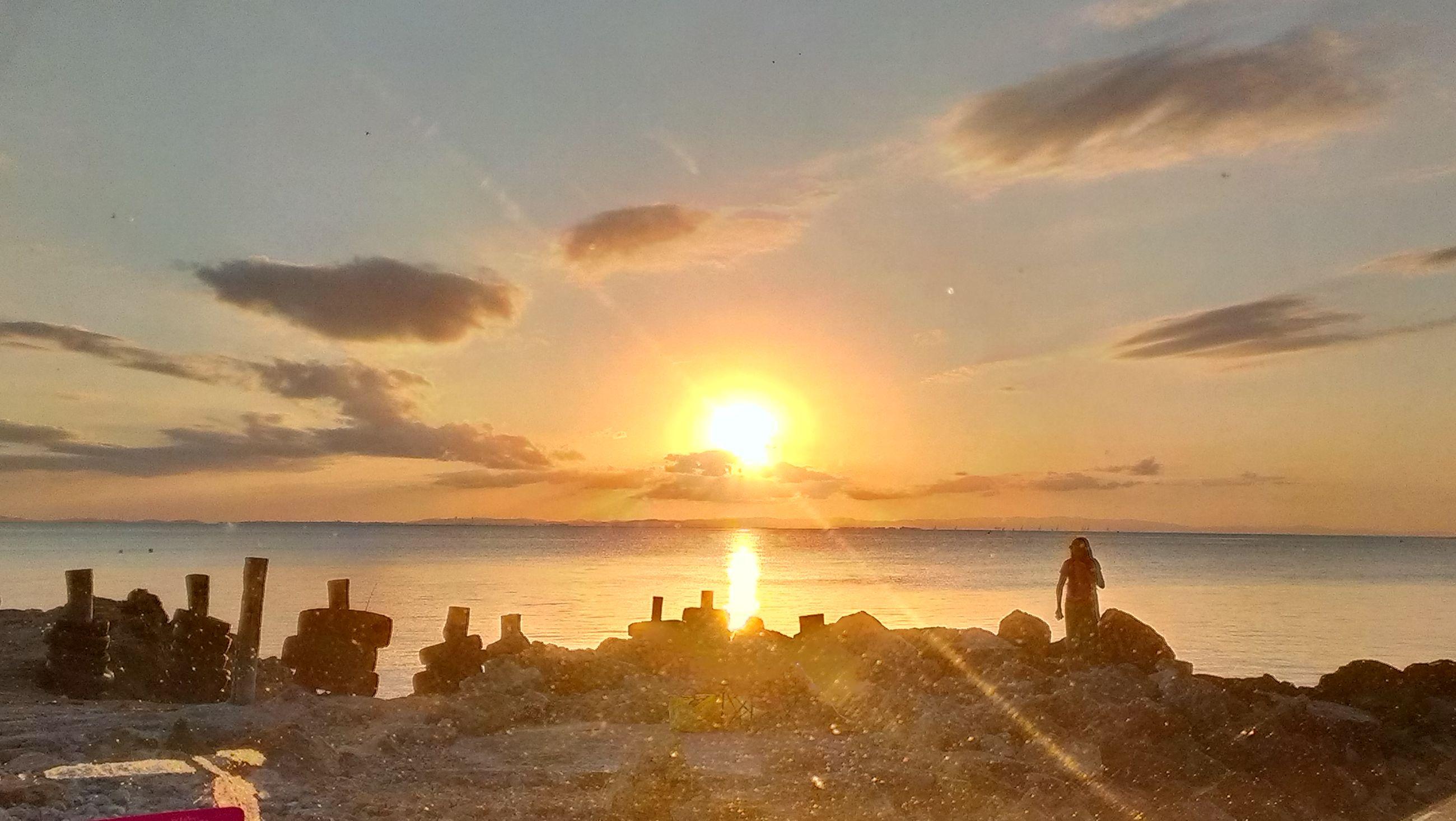 sunset, water, sea, sun, sky, lifestyles, leisure activity, beach, horizon over water, orange color, scenics, beauty in nature, person, men, shore, sunlight, nature, silhouette, cloud - sky