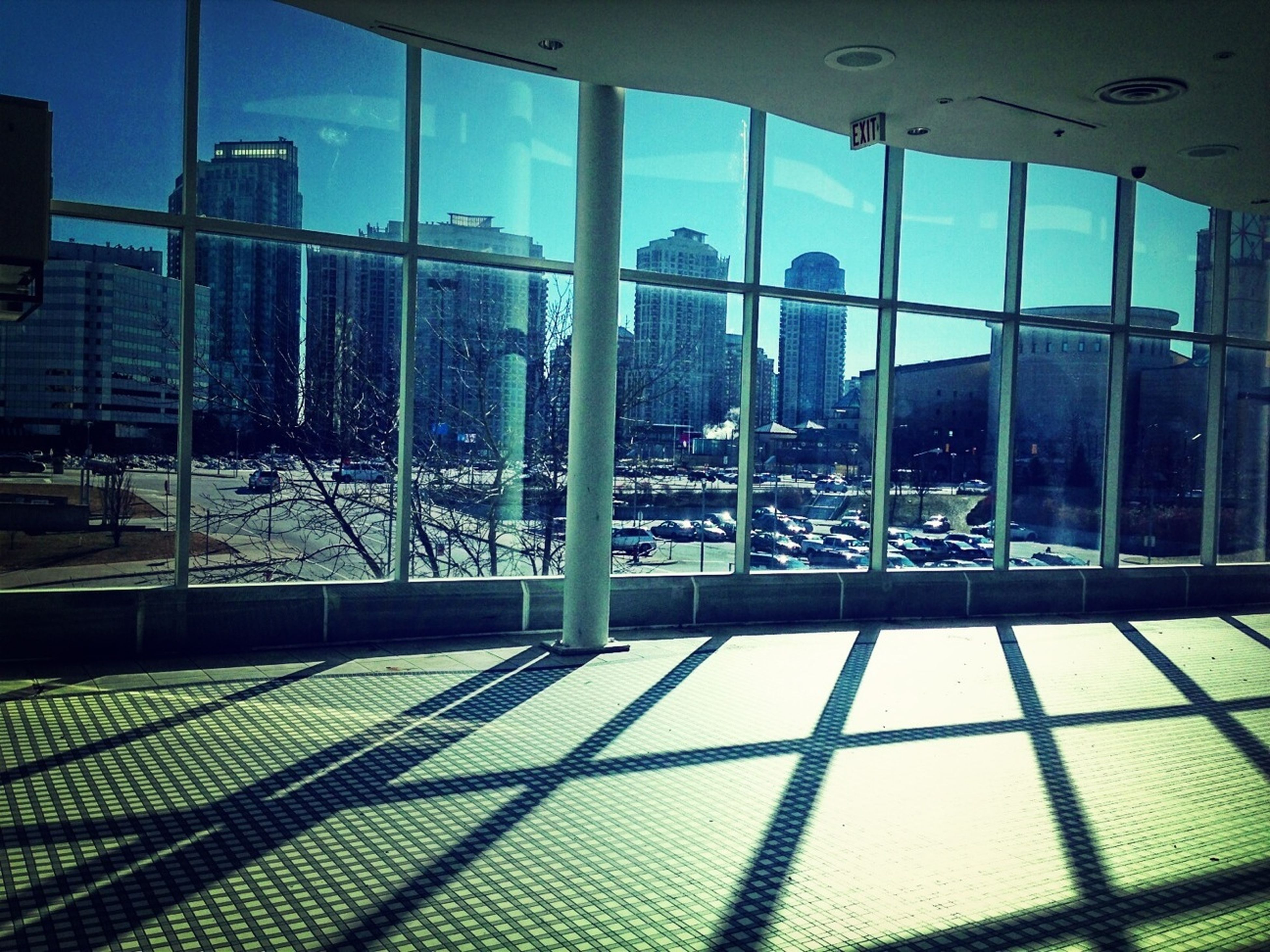 architecture, indoors, built structure, glass - material, window, transparent, building exterior, modern, city, sunlight, chair, blue, empty, absence, day, shadow, office building, reflection, glass, railing