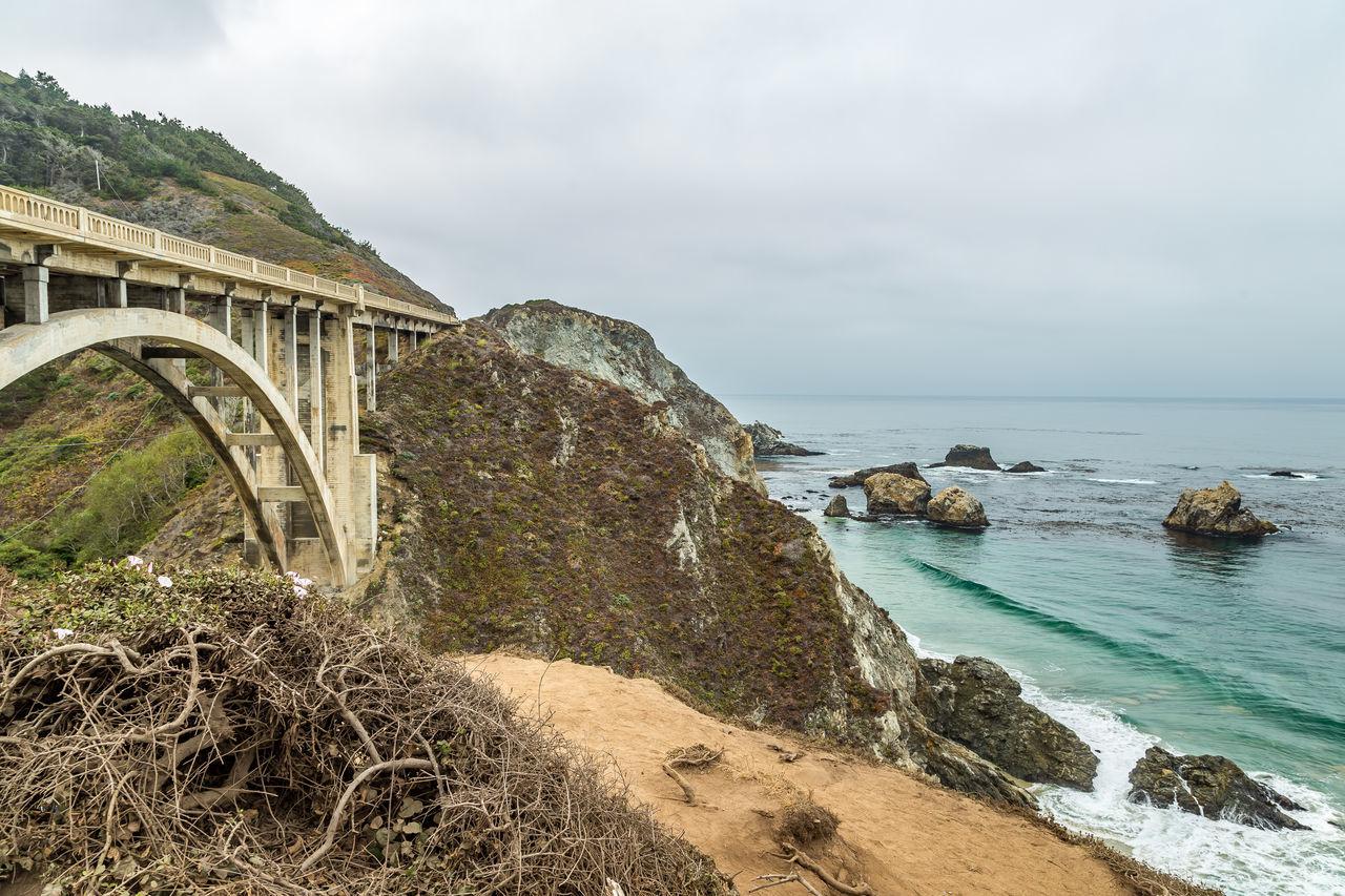 Beauty In Nature Bridge Cloud - Sky Cloudy Rock Rock - Object Sea Sky Water