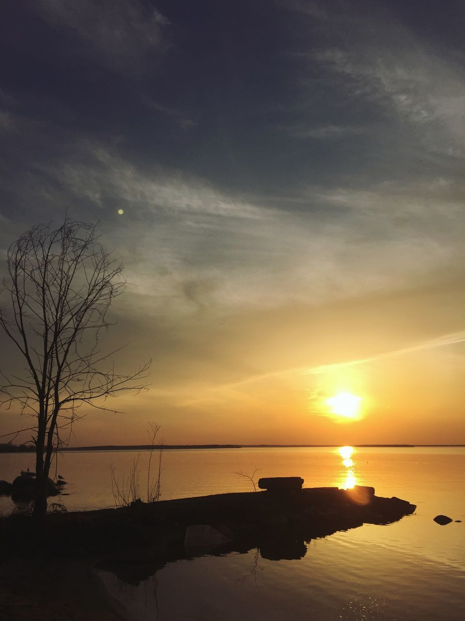sunset, reflection, tranquility, scenics, beauty in nature, tranquil scene, nature, water, sky, sun, outdoors, lake, silhouette, bare tree, no people, horizon over water, tree, day
