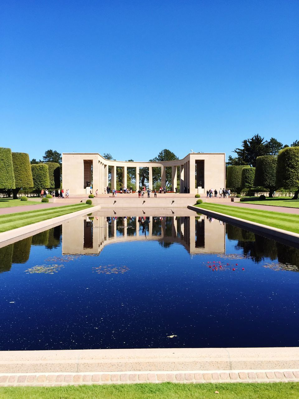 built structure, architecture, reflection, blue, history, building exterior, clear sky, water, day, tree, outdoors, old ruin, ancient, sunlight, reflecting pool, grass, swimming pool, ancient civilization, no people, nature, sky