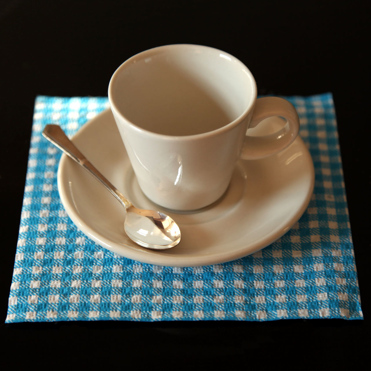 High Angle View Of Empty Crockery On Blue Napkin Against Black Background