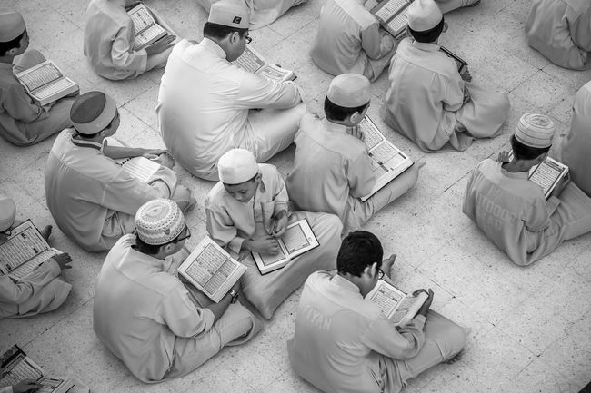 A group of Muslim Students reading the Quran. Black And White Islam Kids Koran Kuala Lumpur Learning Malaysia Muslim People Quran Reading Students Talking Top Down