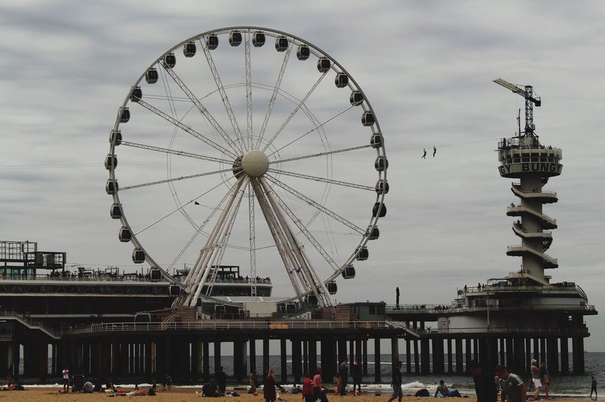 Like if you it Architecture Built Structure Ferris Wheel Building Exterior Sky Scheveningen  Cloud - Sky Day Amusement Park Travel Destinations Outdoors City Arts Culture And Entertainment Low Angle View Amusement Park Ride Real People Nautical Vessel Men People