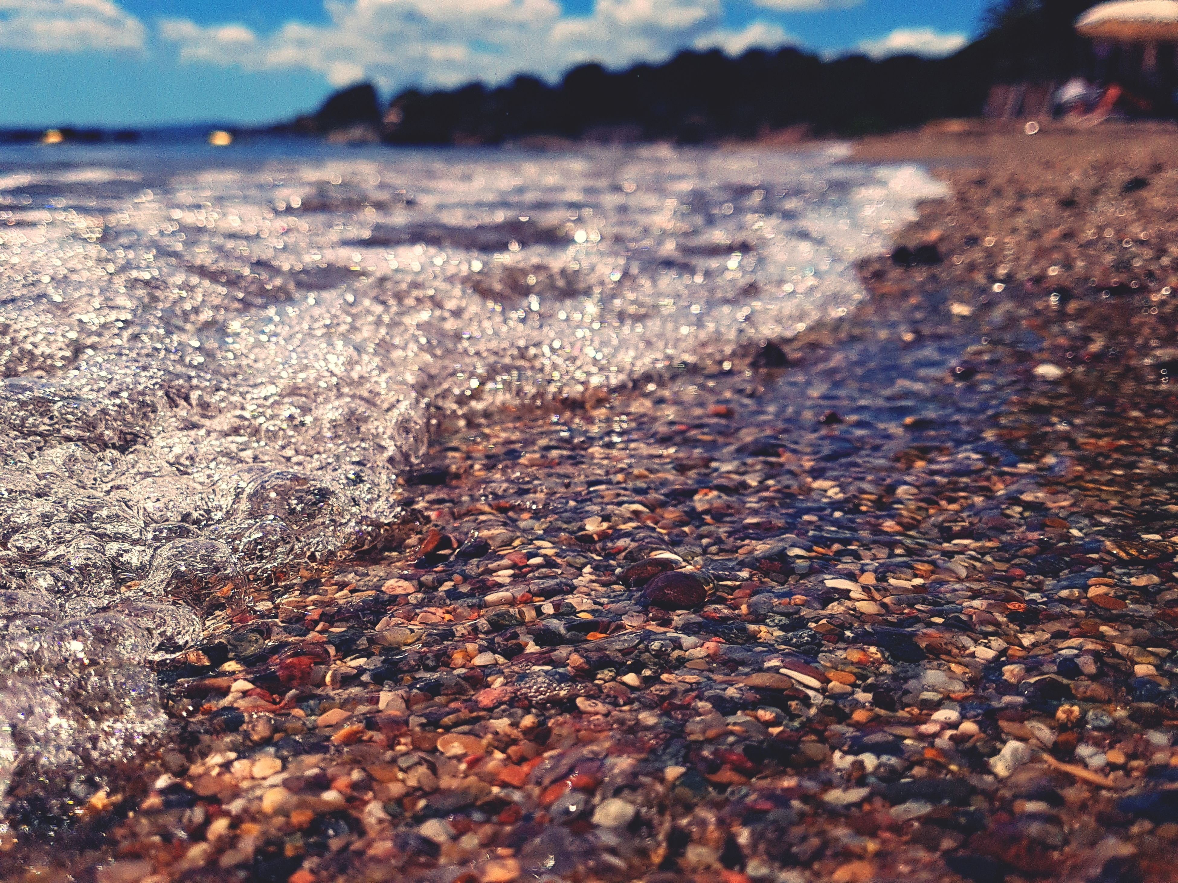 low section, surface level, outdoors, nature, day, tranquility, beauty in nature, sunlight, water, close-up, scenics, beach, human body part, one person, pebble beach, people