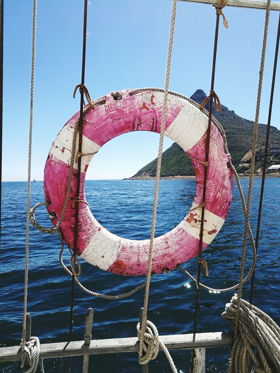 water, nautical vessel, rope, mode of transport, transportation, sea, boat, life belt, tied up, no people, safety, sky, day, nature, outdoors, moored, beauty in nature, sailing, hanging, clear sky, scenics, sailboat, close-up, boat deck