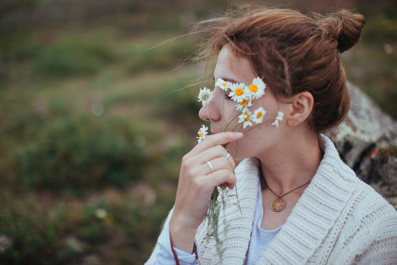 flower, real people, one person, leisure activity, focus on foreground, lifestyles, outdoors, young adult, day, headshot, holding, young women, women, nature, close-up, flower head, fragility, freshness, people