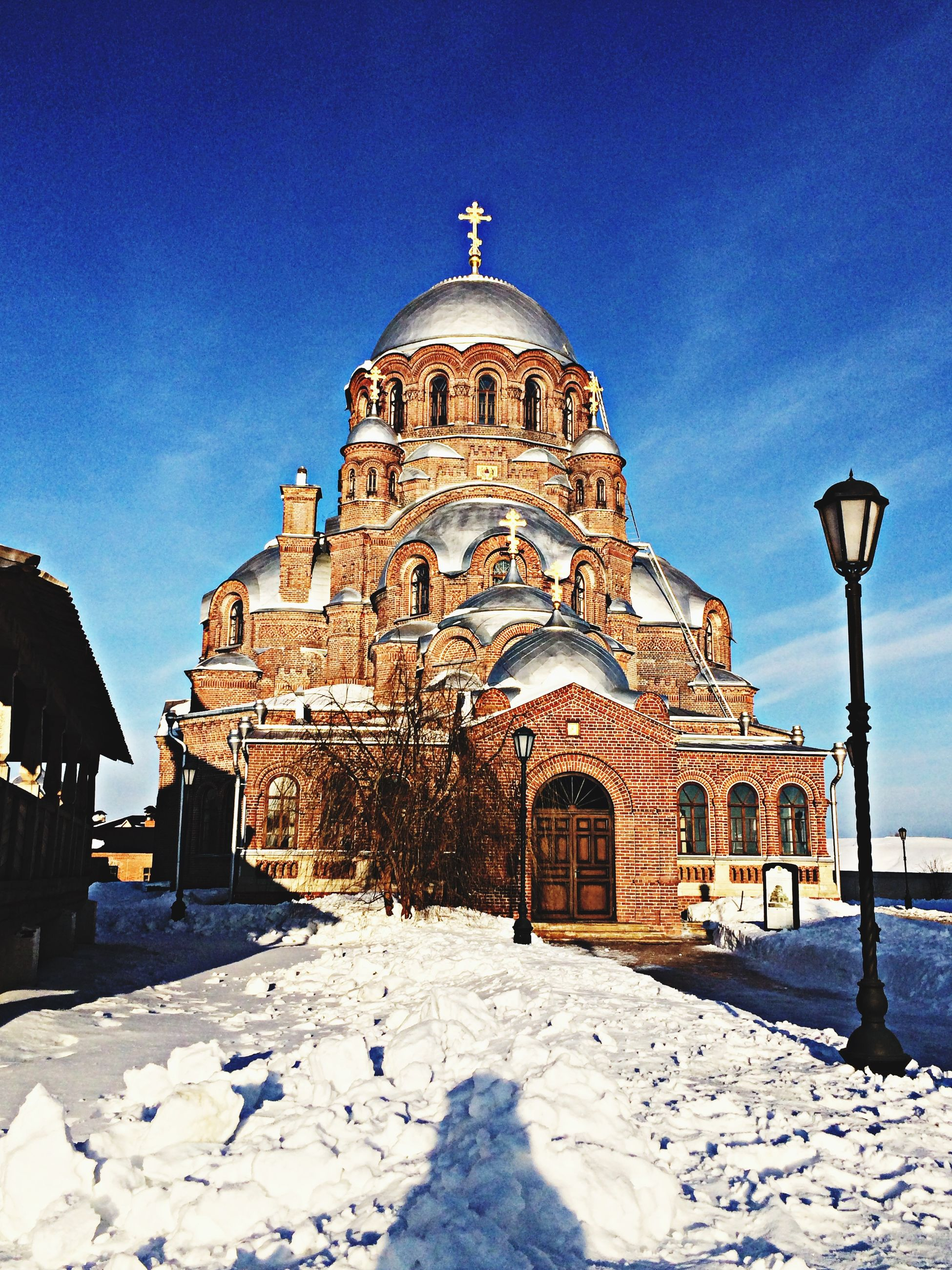building exterior, architecture, place of worship, built structure, religion, spirituality, church, blue, dome, sky, cathedral, facade, cross, clear sky, travel destinations, famous place, snow, incidental people