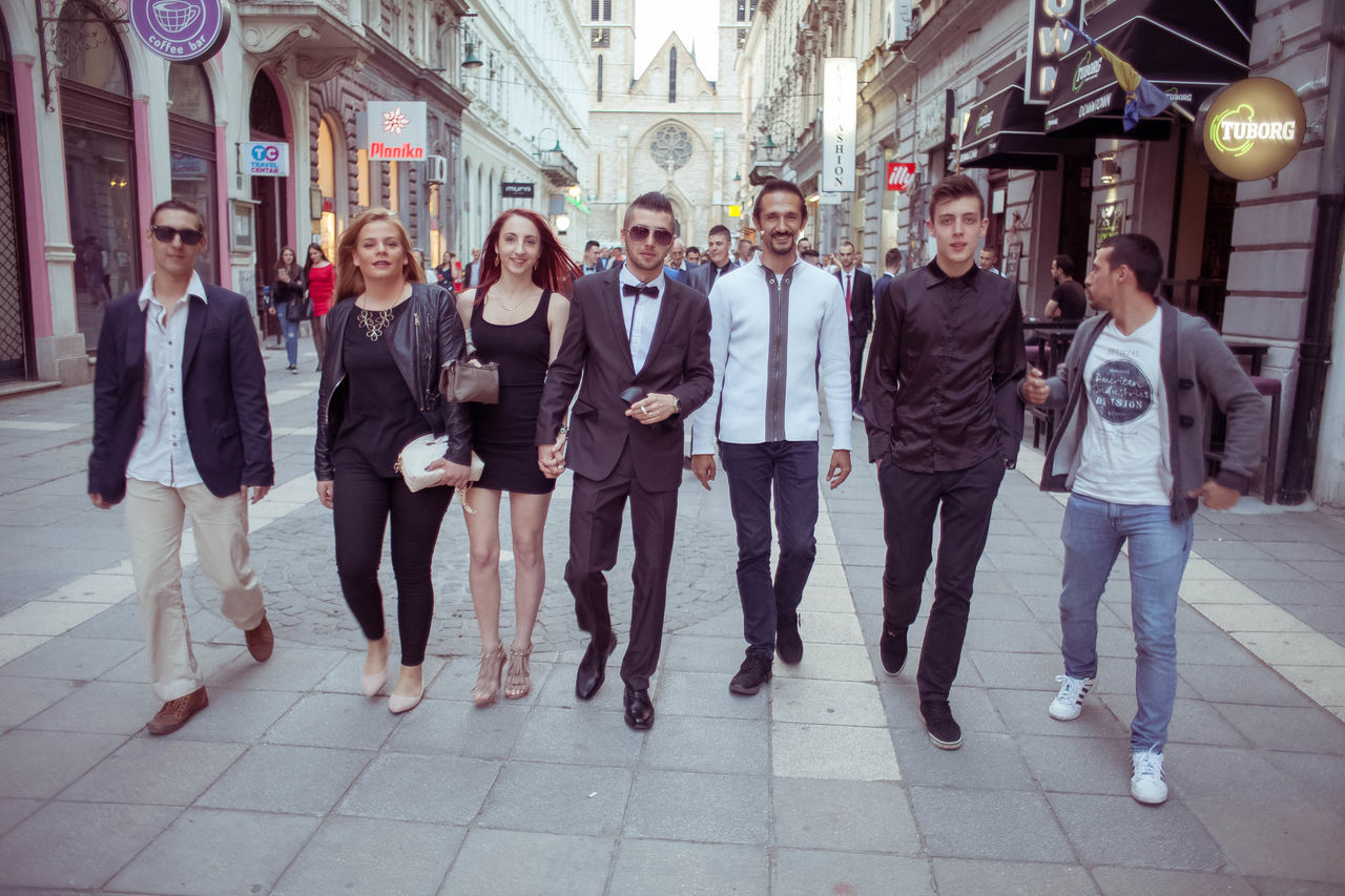 full length, looking at camera, men, front view, mid adult, portrait, togetherness, women, large group of people, young women, city, adult, young adult, standing, architecture, day, people, outdoors, building exterior, adults only, crowd