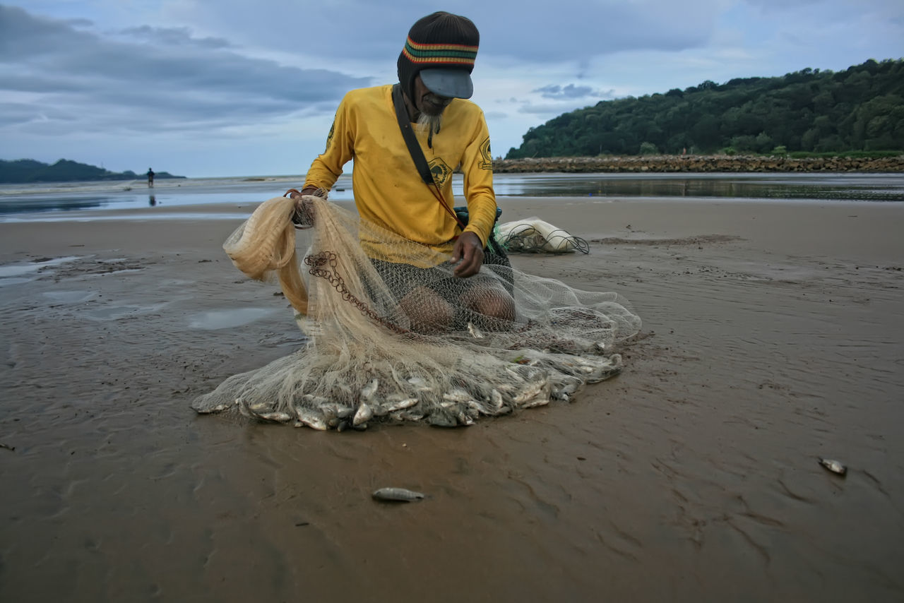 traditional fisherman in pacitan eastjava Indonesia Beach Beauty In Nature Day Fish Fisherman Nature Nautical Vessel One Person Outdoors Real People Sand Scenics Sea Shore Sky Water