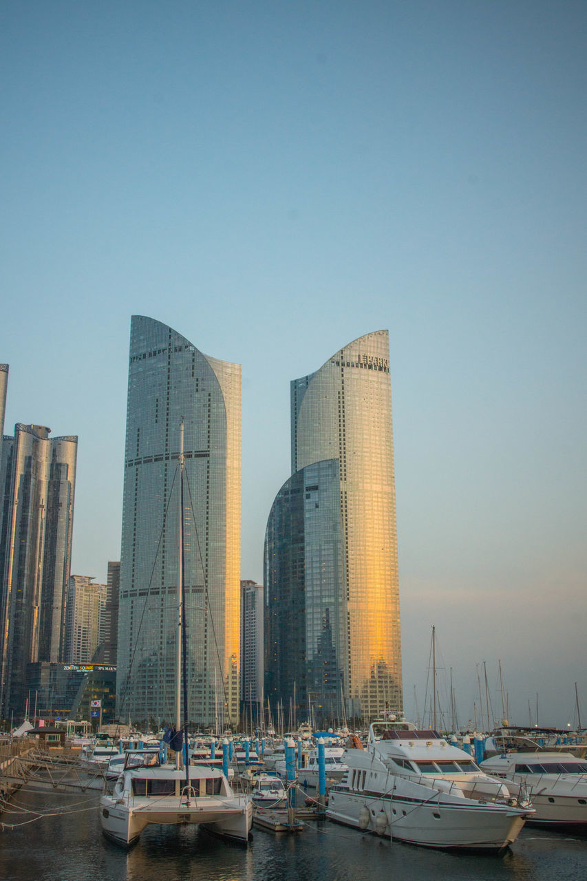 architecture, clear sky, built structure, building exterior, modern, nautical vessel, water, outdoors, sky, day, no people, city
