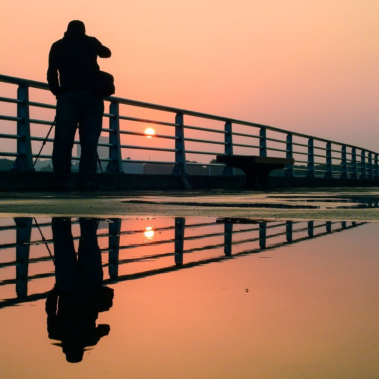 sunset, silhouette, reflection, bridge - man made structure, orange color, water, railing, real people, sky, men, standing, full length, river, lifestyles, waterfront, walking, architecture, outdoors, nature, clear sky, modern, one person, footbridge, beauty in nature, city, day, people