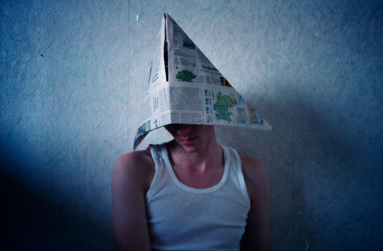 Pensive man wearing newspaper hat