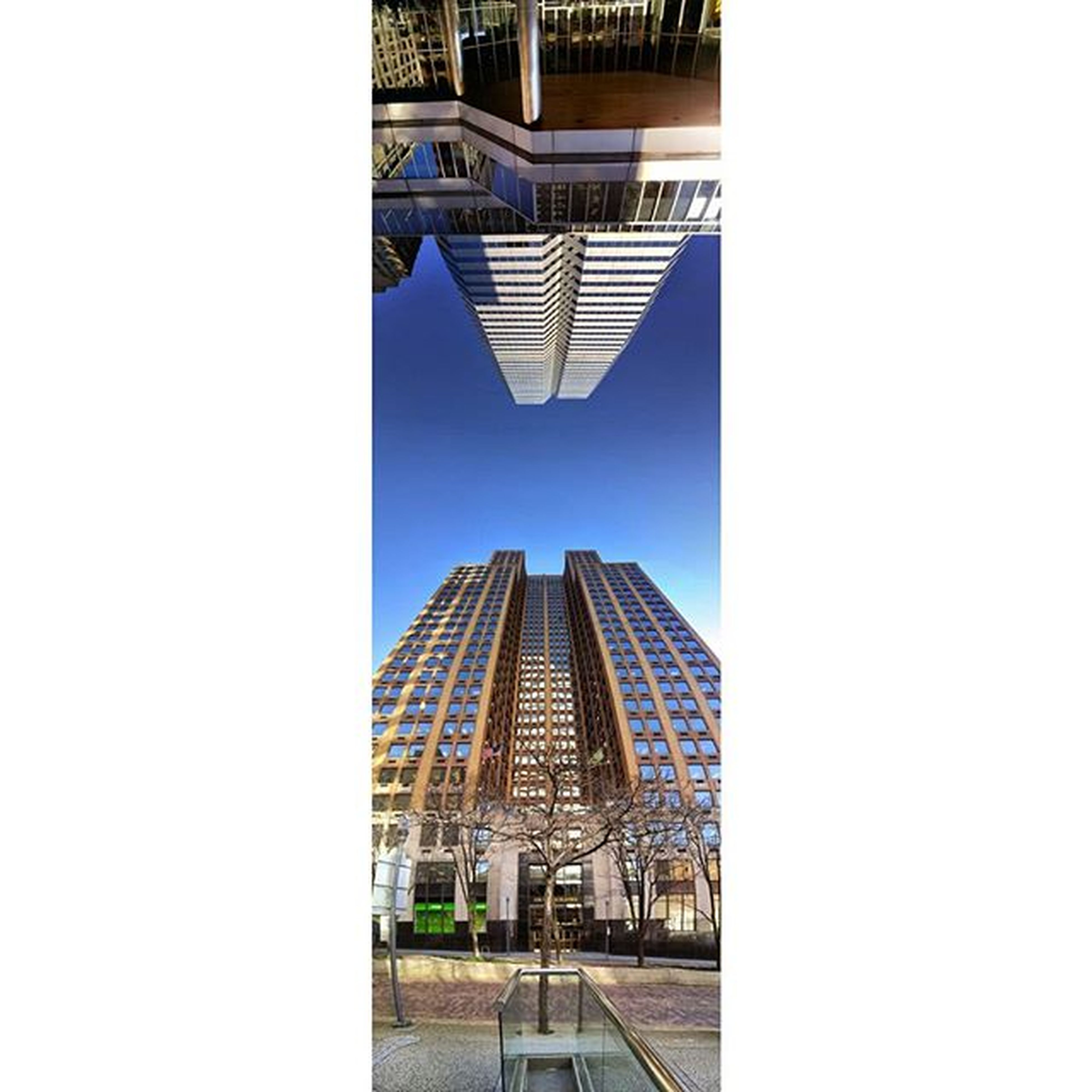 architecture, built structure, building exterior, modern, city, clear sky, office building, skyscraper, tower, tall - high, building, low angle view, city life, capital cities, famous place, travel destinations, glass - material, day, architectural feature, copy space