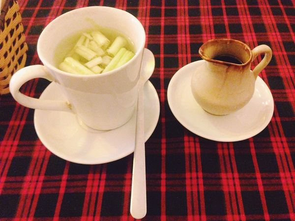 A hot cup of lemongrass tea, served with a little jug of syrup on the red and black plaid tablecloth Food And Drink Refreshment Table Drink Indoors  Close-up Tea Lemongrass Tea Red And Black Plaid Tablecloth Spoon Sapa, Vietnam