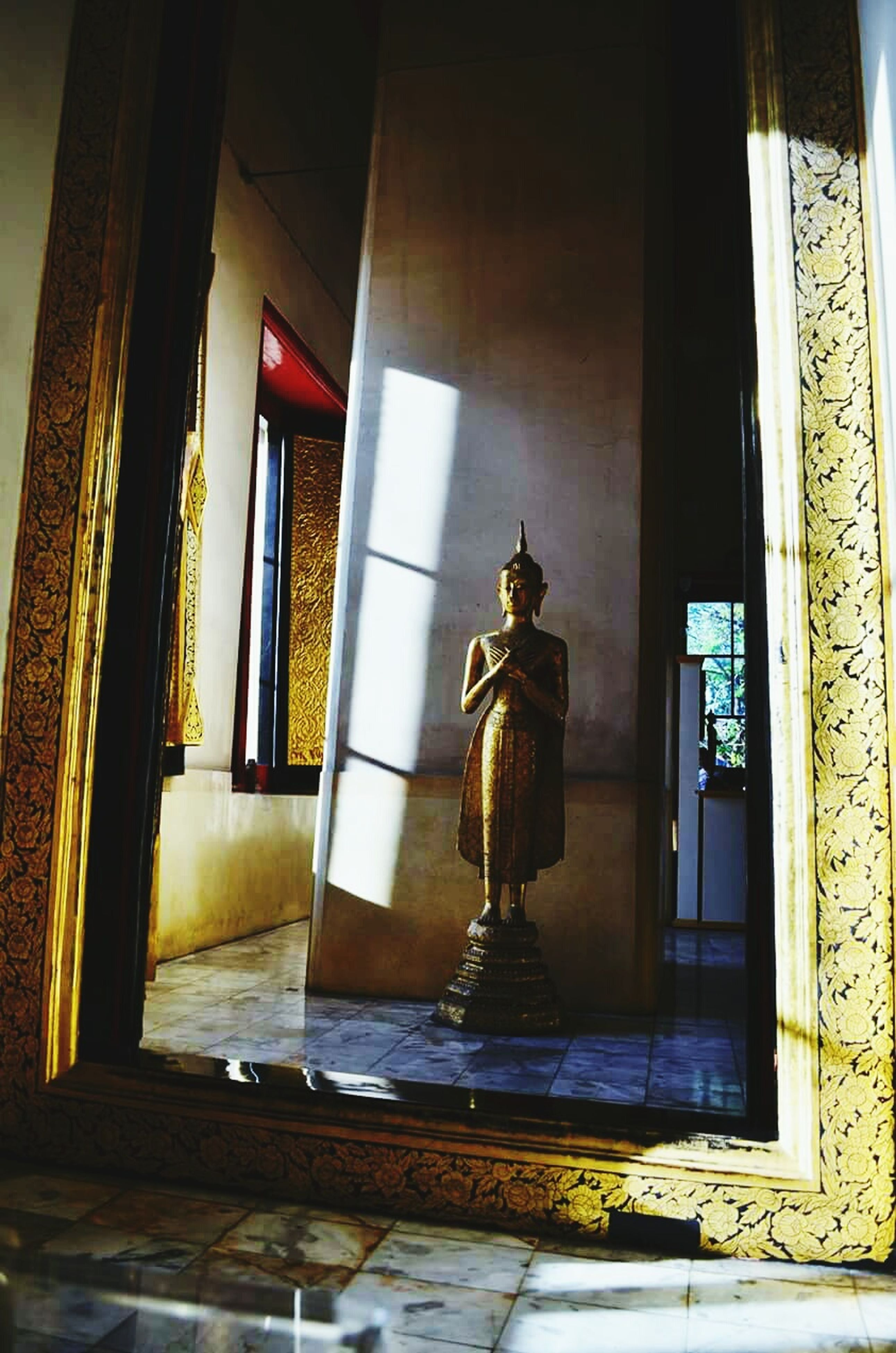 indoors, statue, human representation, art and craft, art, sculpture, architecture, built structure, creativity, window, religion, spirituality, no people, low angle view, door, place of worship, carving - craft product, sunlight