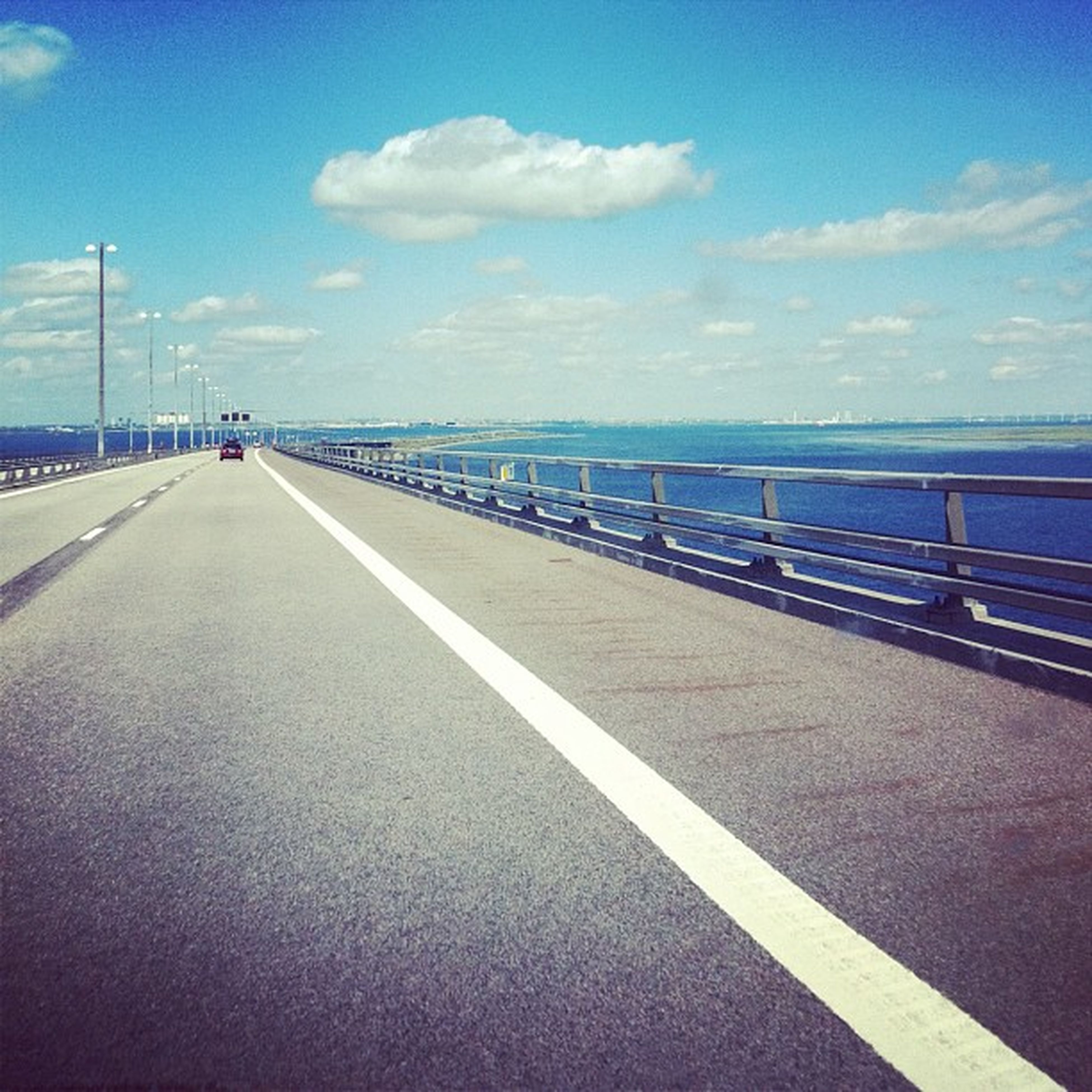 sky, transportation, the way forward, sea, diminishing perspective, water, railing, road, road marking, vanishing point, cloud - sky, cloud, blue, built structure, connection, incidental people, long, outdoors, empty, day