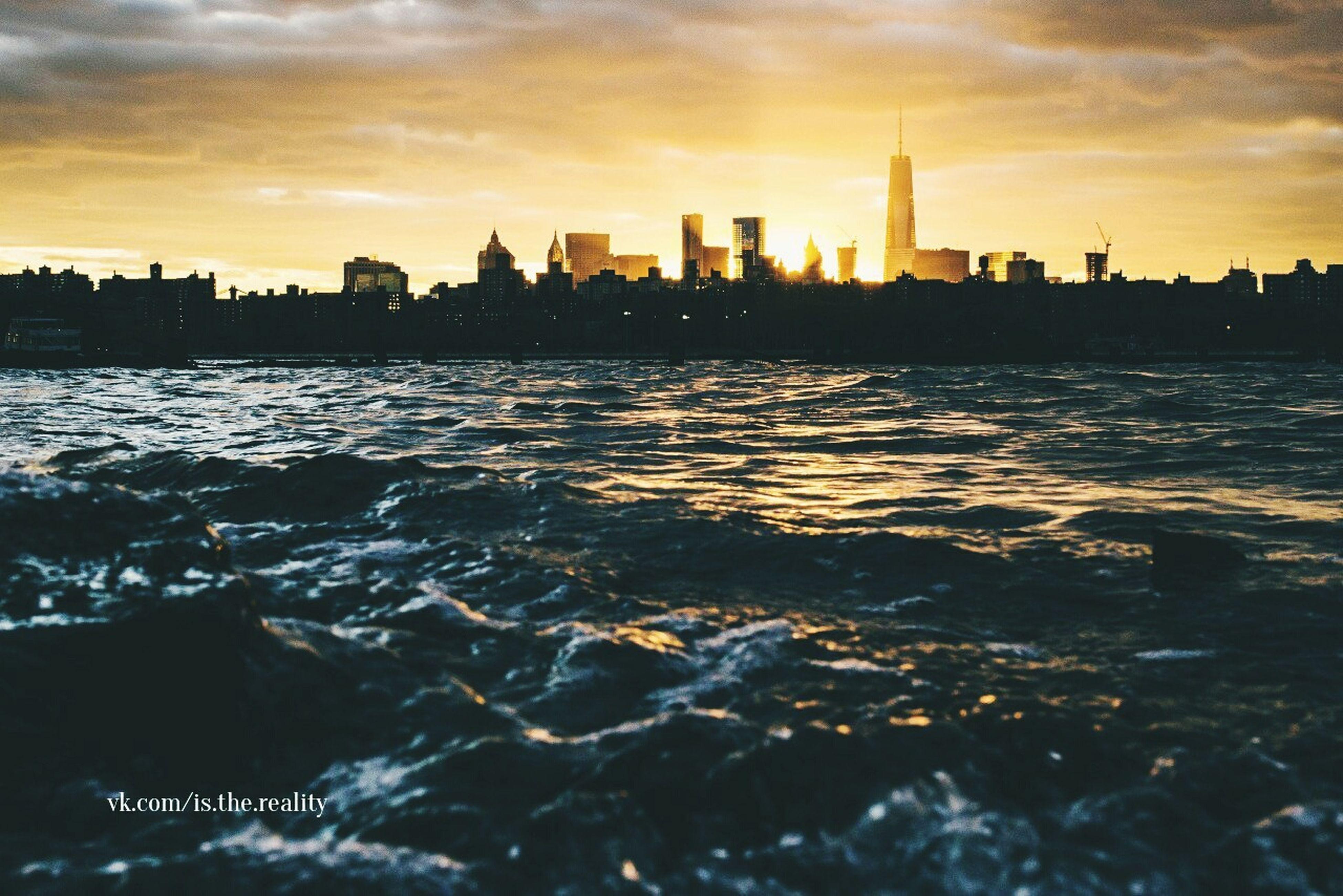 sunset, water, building exterior, architecture, built structure, sky, sea, city, waterfront, silhouette, skyscraper, cityscape, cloud - sky, orange color, urban skyline, tower, scenics, dusk, rippled, river
