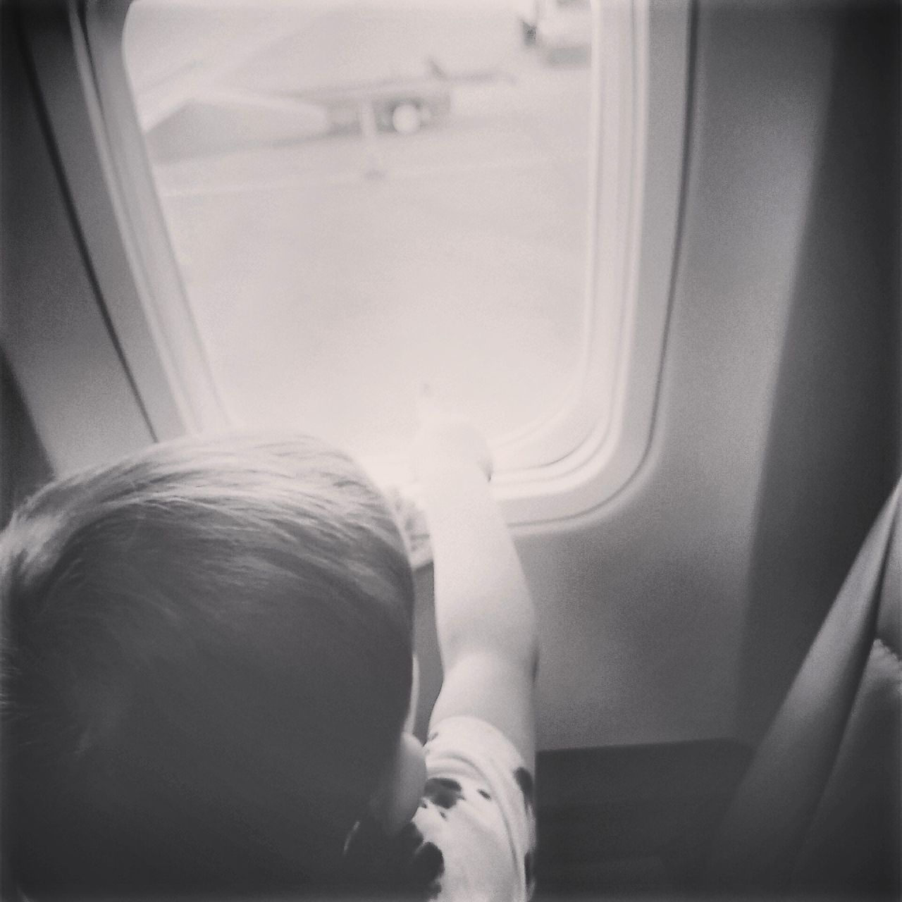 vehicle interior, transportation, one person, childhood, vehicle seat, real people, window, journey, mode of transport, sitting, airplane, indoors, day, close-up, people