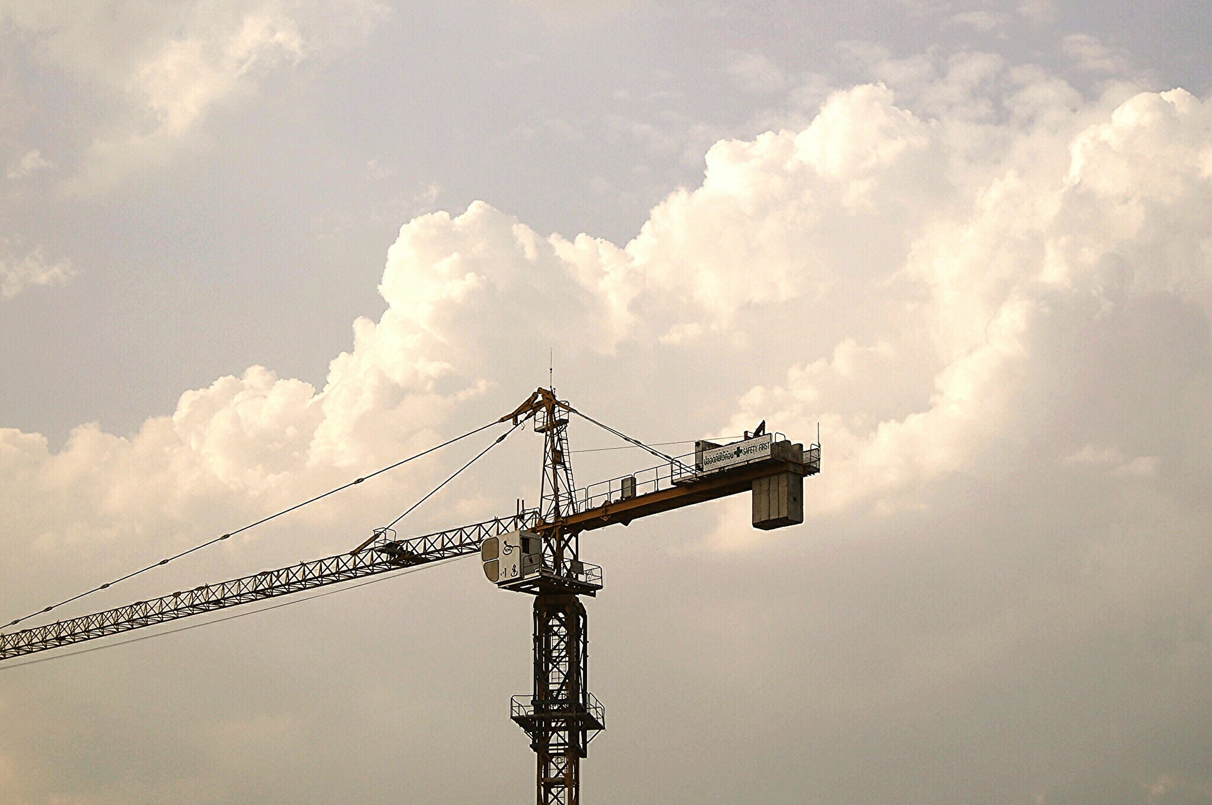 low angle view, sky, crane - construction machinery, construction site, cloud - sky, development, crane, built structure, cloudy, connection, communication, technology, cloud, construction, industry, silhouette, tall - high, fuel and power generation, metal, architecture