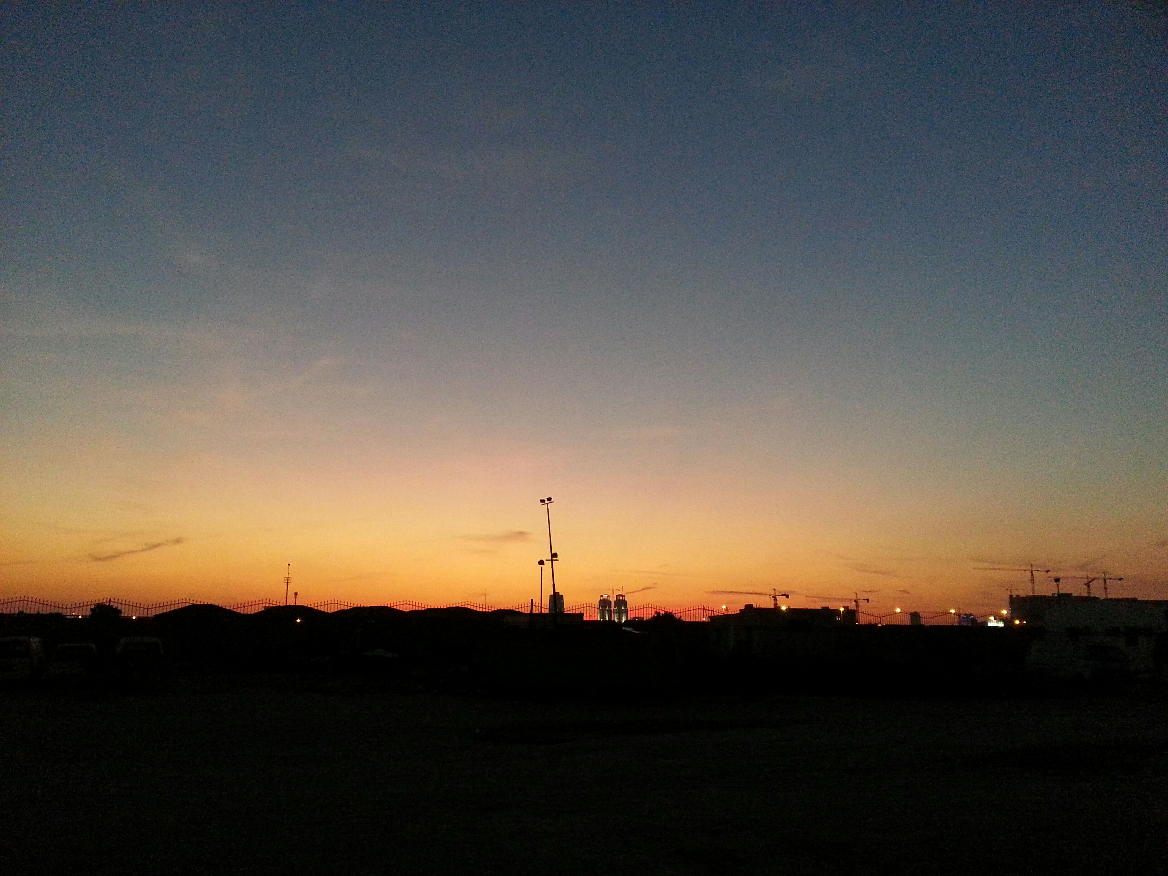 sunset, silhouette, copy space, orange color, clear sky, landscape, scenics, tranquility, tranquil scene, dusk, sky, beauty in nature, dark, built structure, nature, building exterior, outdoors, architecture, blue, idyllic