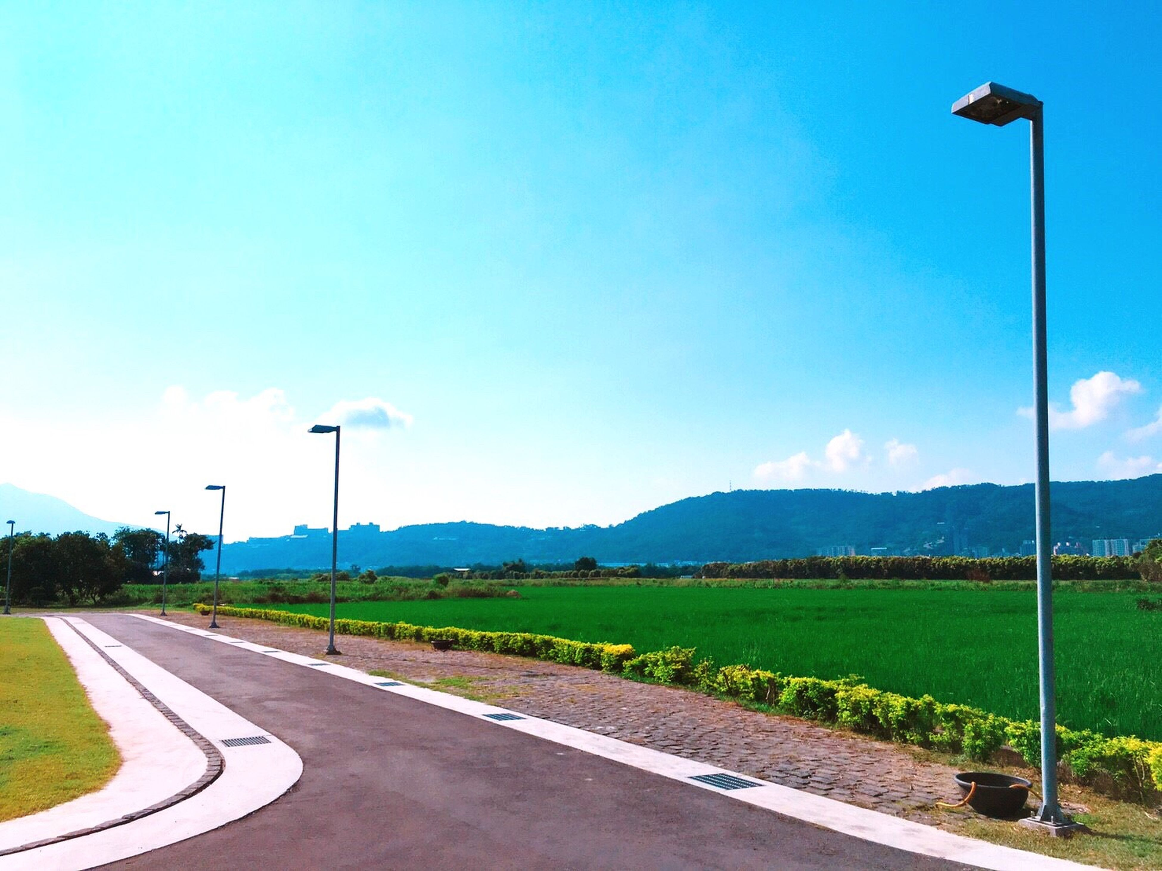 road, transportation, empty, the way forward, clear sky, landscape, street, road marking, tranquility, solitude, tranquil scene, pole, mountain, day, dividing line, long, country road, outdoors, blue, empty road, mountain range, curve, nature, countryside, scenics, vanishing point, surface level, diminishing perspective, beauty in nature, non-urban scene
