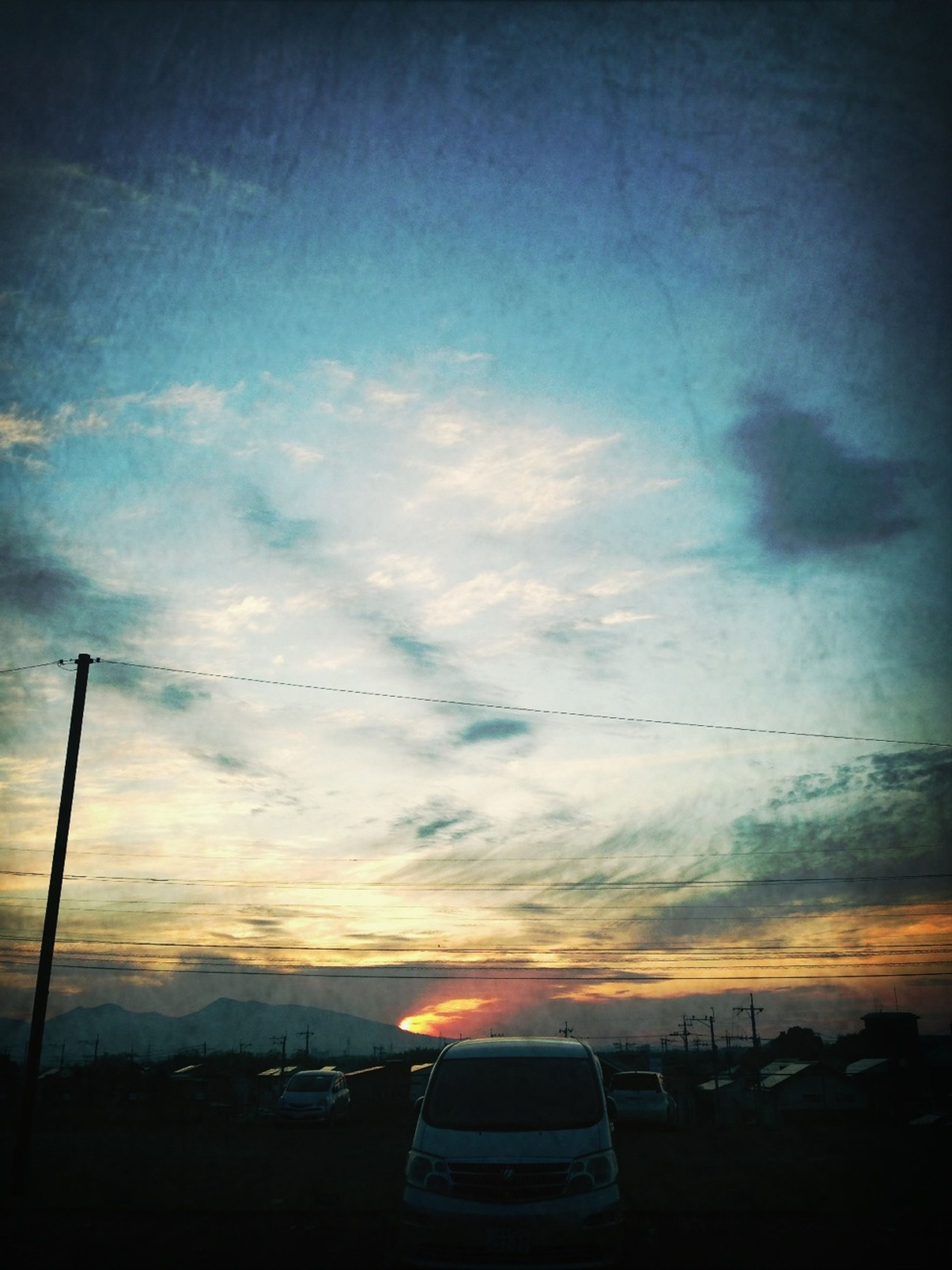sunset, sky, silhouette, cloud - sky, transportation, beauty in nature, scenics, mode of transport, cloud, cloudy, car, nature, tranquility, orange color, tranquil scene, dusk, dramatic sky, street light, low angle view, land vehicle