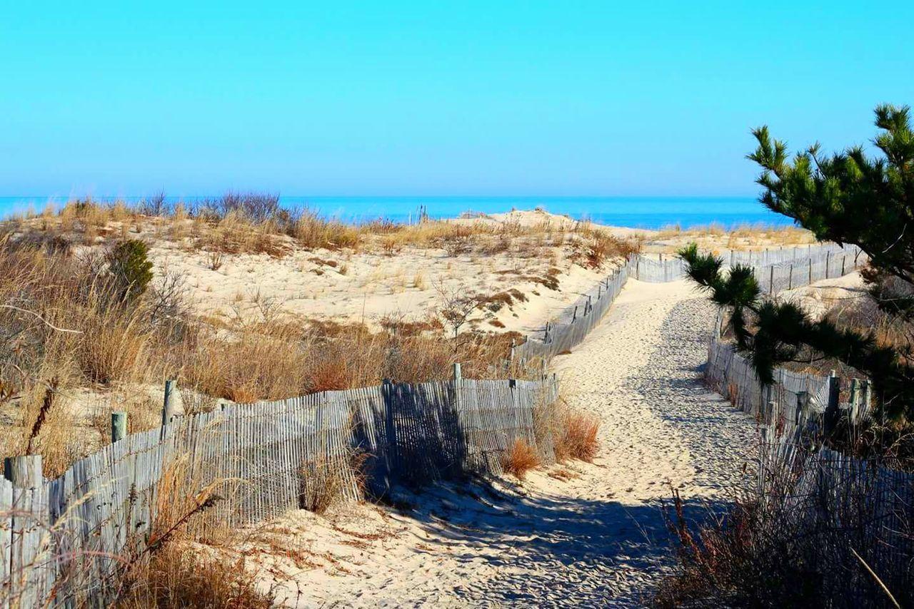 Dirt Road Leading Towards Beach Against Blue Sky