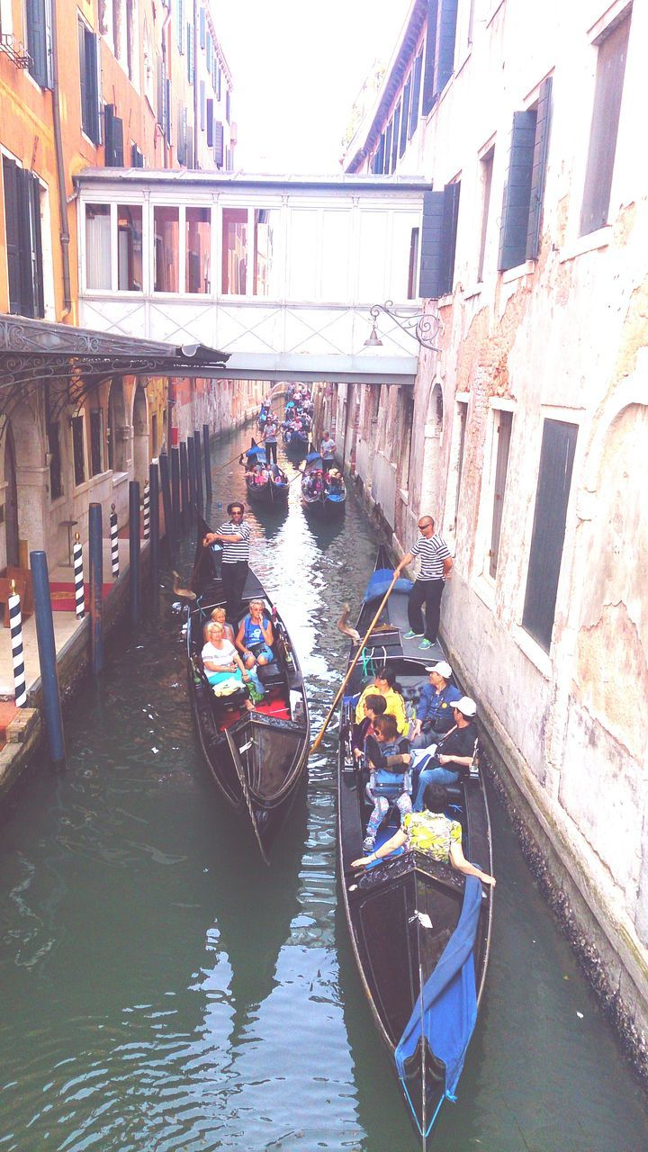 architecture, transportation, building exterior, canal, real people, nautical vessel, built structure, mode of transport, men, day, gondola, outdoors, gondolier, water, gondola - traditional boat, oar, large group of people, rowing, adult, people