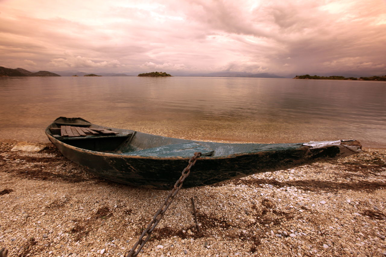 Abandoned Boat Moored On Beach Against Cloudy Sky