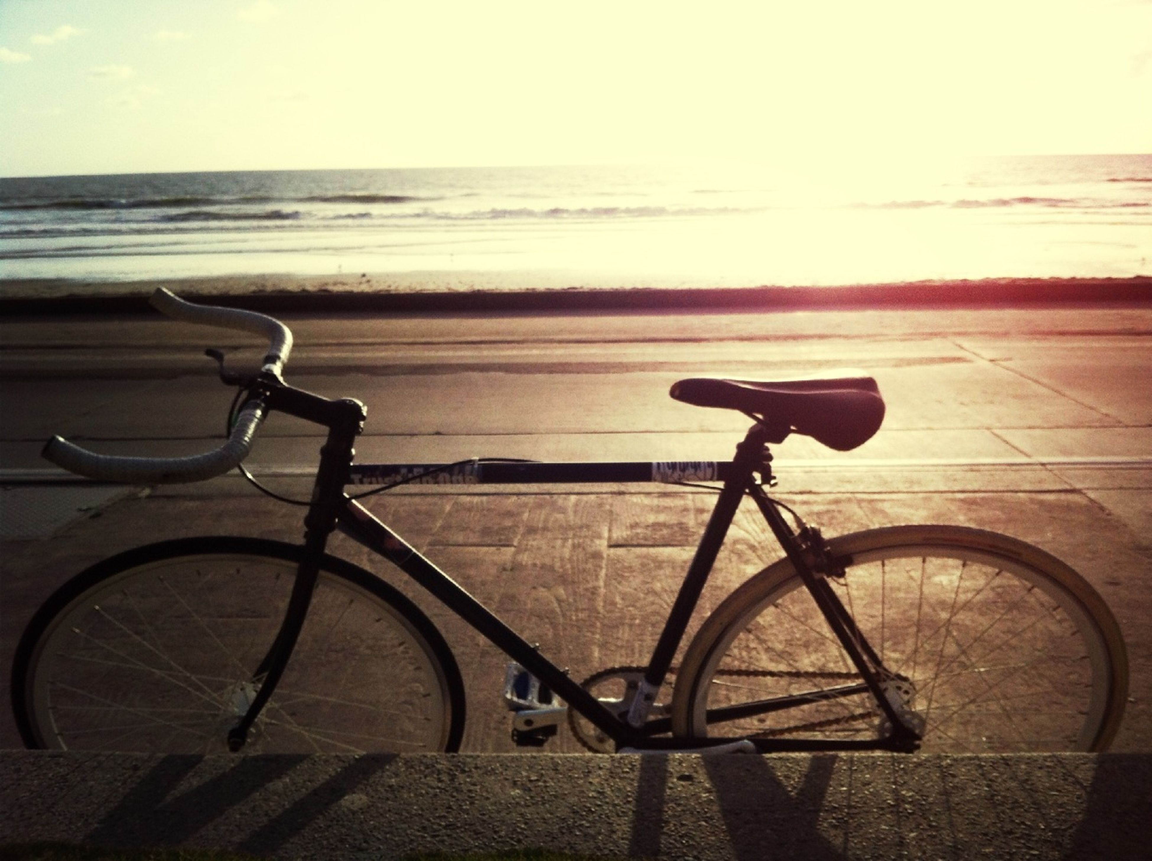 sea, horizon over water, water, bicycle, sky, tranquility, absence, railing, tranquil scene, sunlight, beauty in nature, beach, scenics, sunset, nature, empty, parking, transportation, no people, shadow