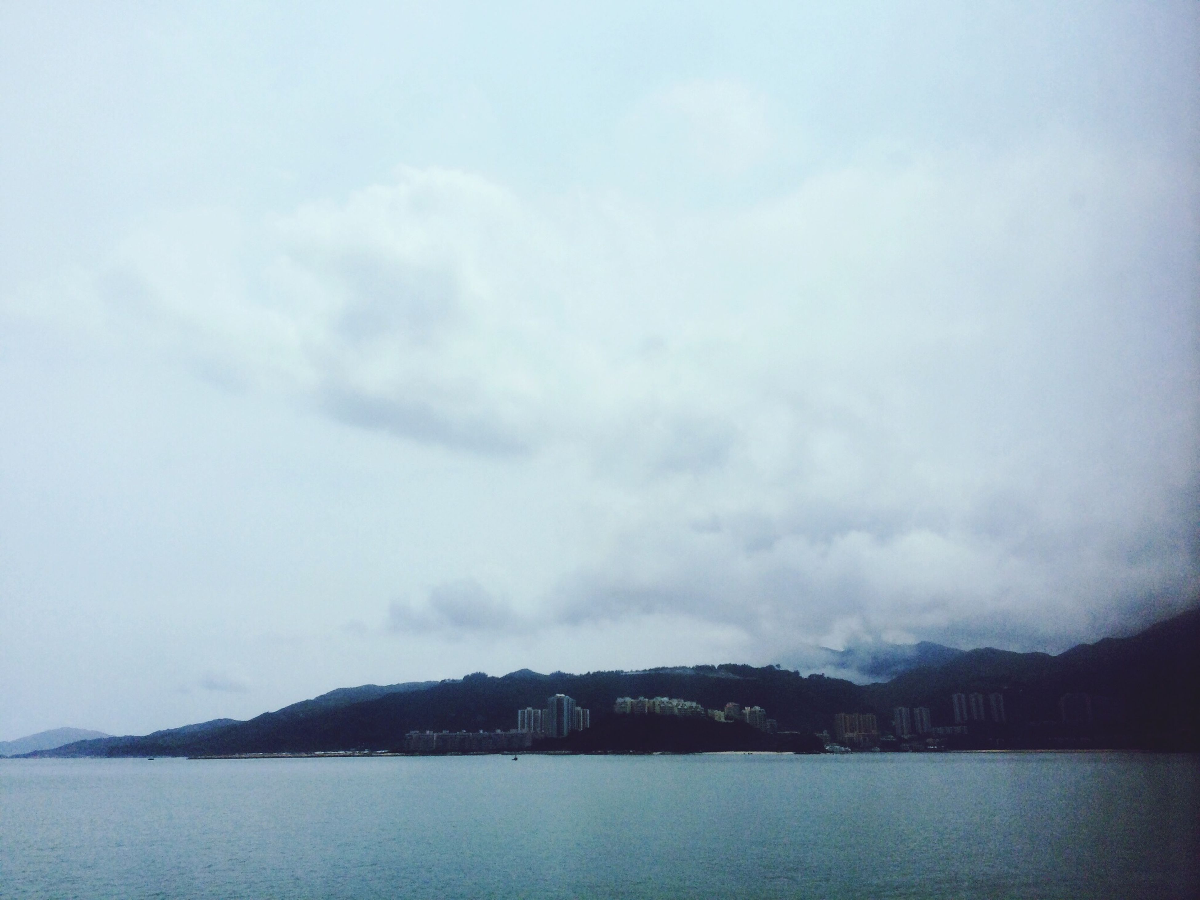 water, sky, waterfront, mountain, scenics, tranquil scene, sea, tranquility, cloud - sky, beauty in nature, nature, built structure, mountain range, architecture, building exterior, river, cloud, cloudy, lake, idyllic
