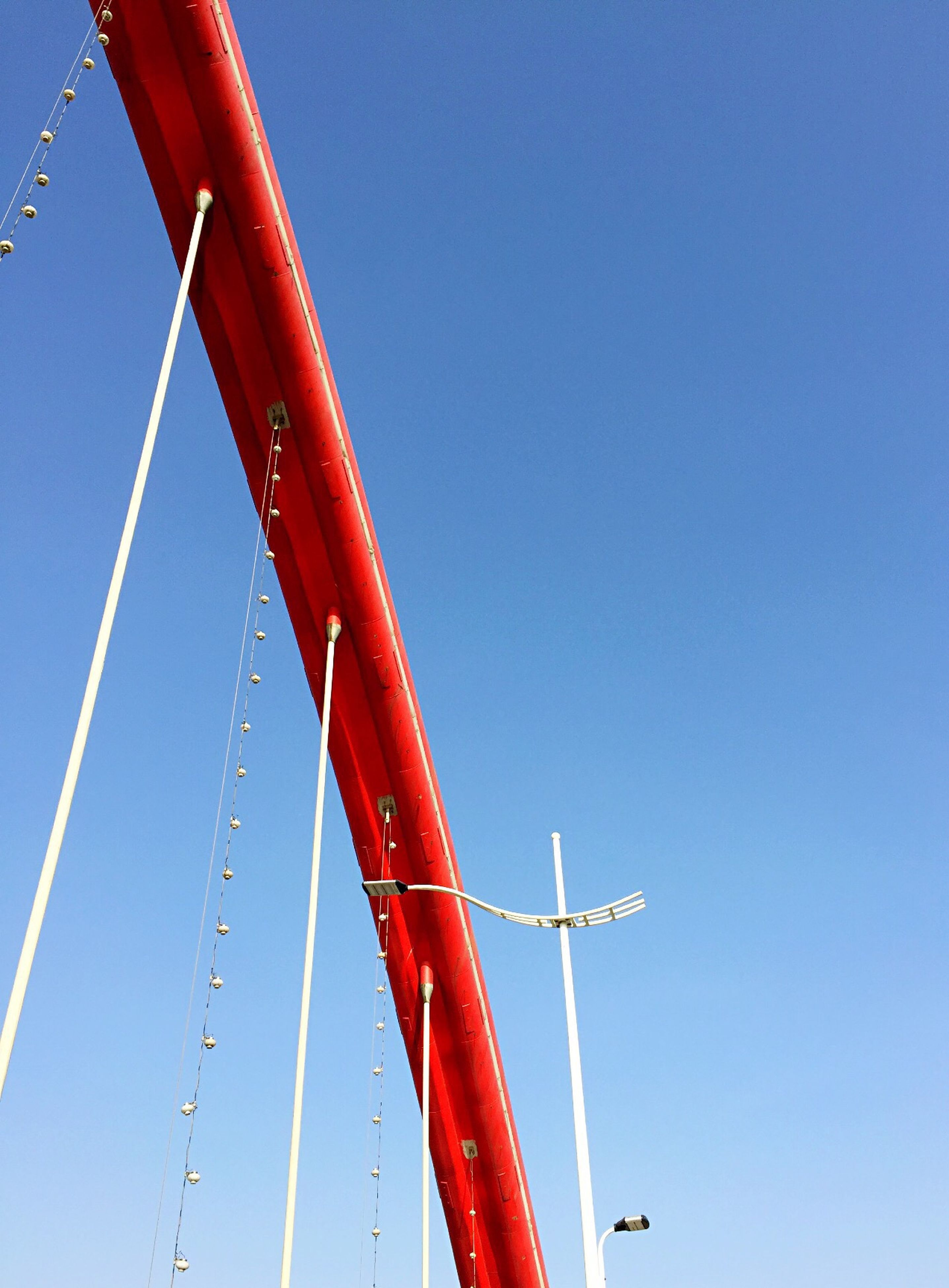 clear sky, low angle view, red, copy space, blue, transportation, connection, outdoors, no people, day, part of, cable, high section, flag, pole, identity, built structure, mode of transport, sky, national flag