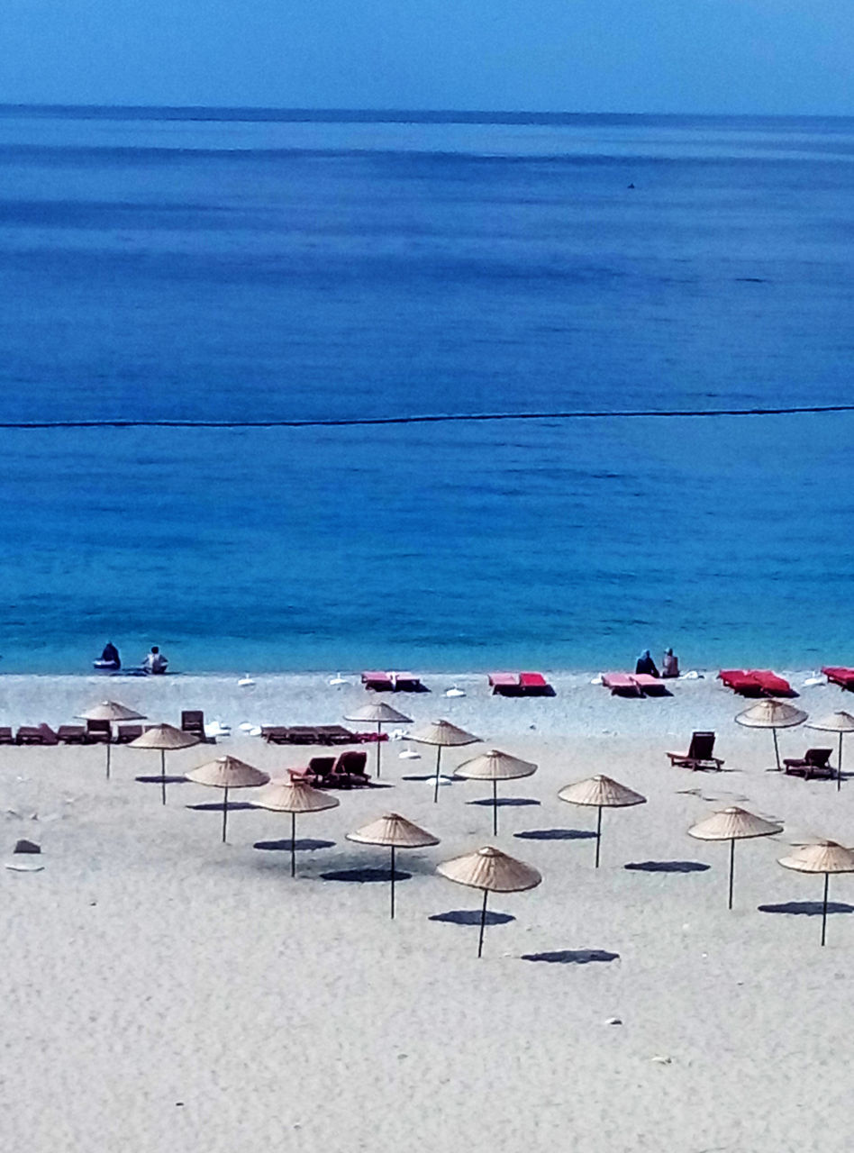 sea, beach, water, sand, horizon over water, nature, beauty in nature, chair, shore, tranquil scene, tranquility, scenics, day, in a row, group of objects, outdoors, sun lounger, large group of objects, no people, table, blue, clear sky, sky