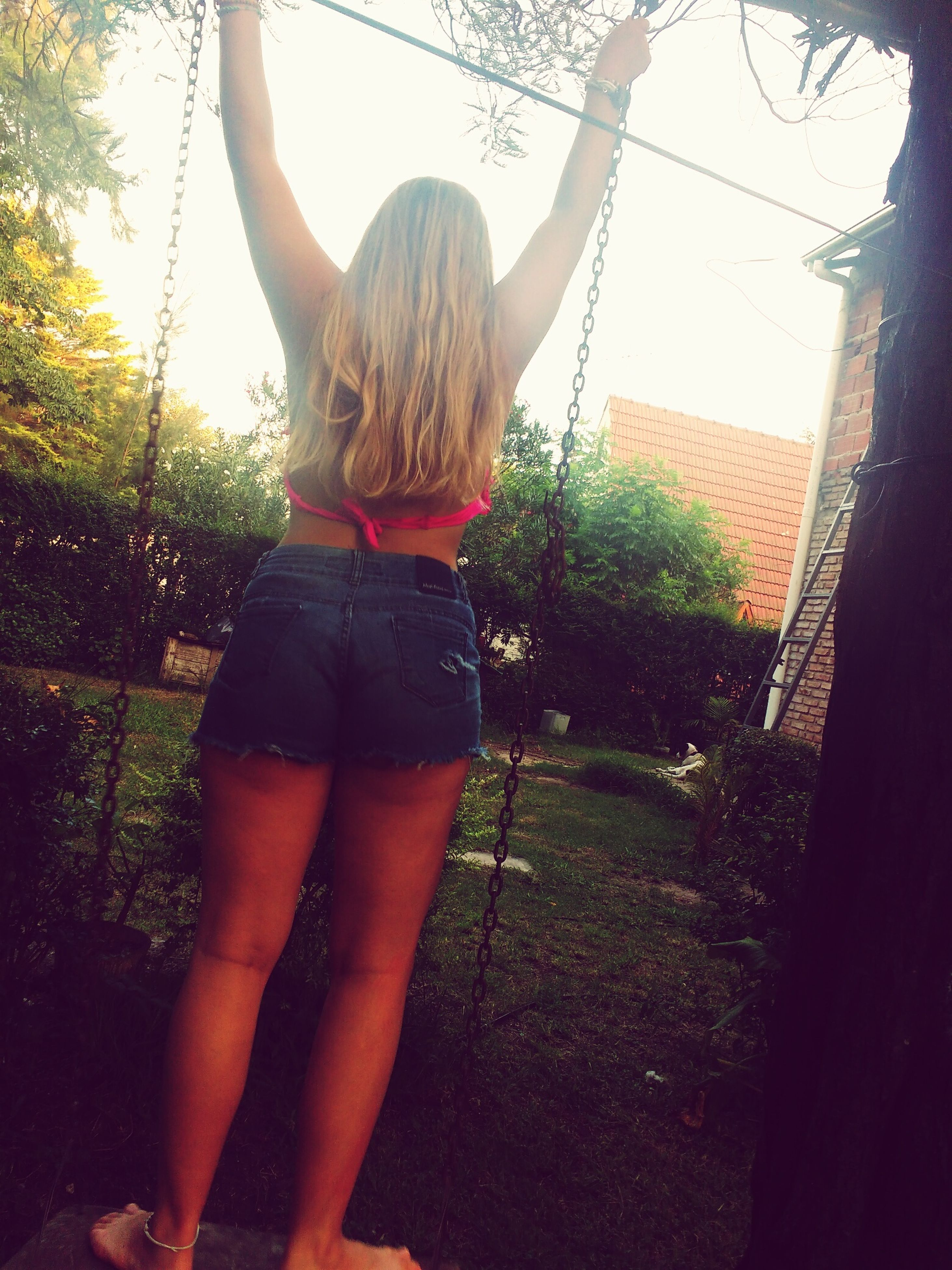 childhood, one person, real people, girls, rear view, tree, elementary age, blond hair, swing, casual clothing, playing, full length, day, leisure activity, front or back yard, outdoors, standing, lifestyles, one girl only, grass, rope swing, sky, people