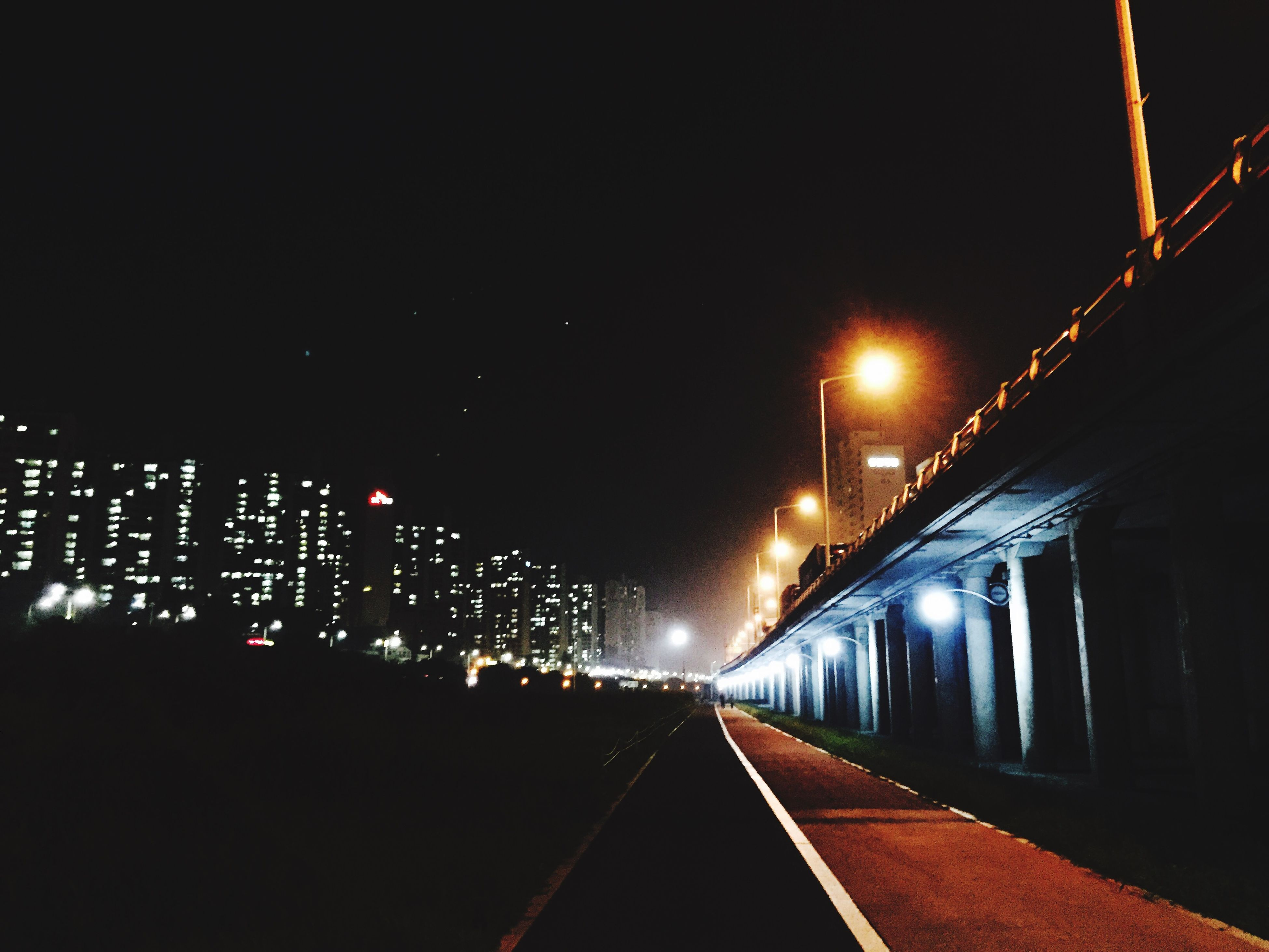 illuminated, night, the way forward, transportation, diminishing perspective, architecture, built structure, vanishing point, railroad track, lighting equipment, building exterior, copy space, city, street light, clear sky, dark, long, sky, rail transportation, tunnel