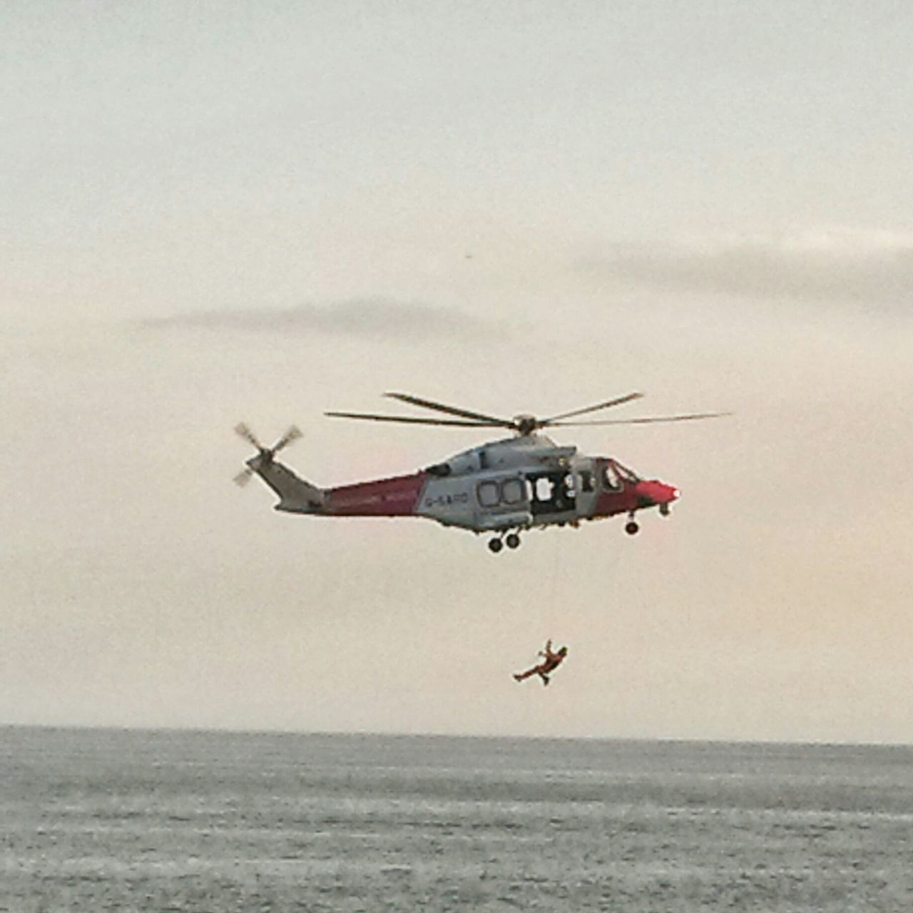 Rescue Worker Hanging From Helicopter Over Sea