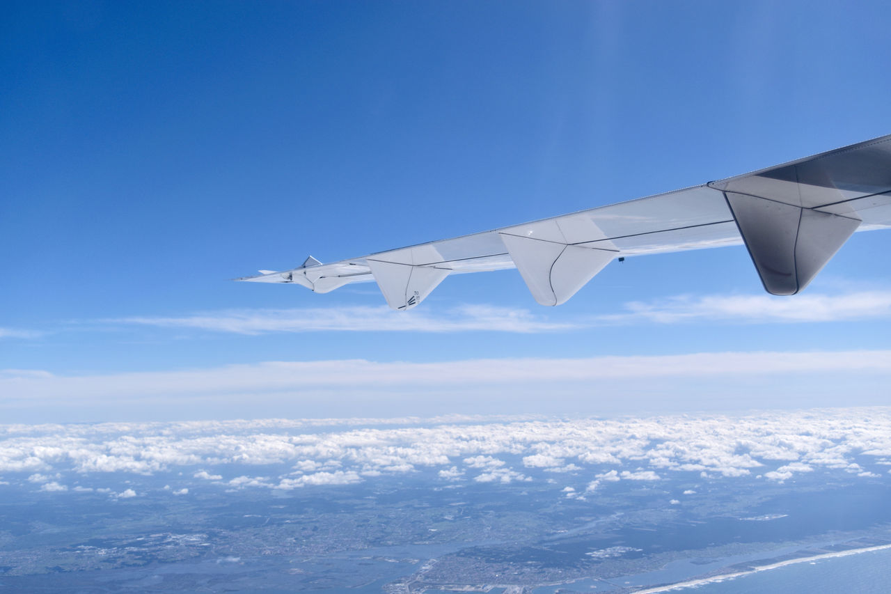 The wing of an airplane flying in the sky Aircraft Airplane Altitude Blue Blue Sky Cloud Day Flying Flying High Horizon Outdoors Panorama Plane Skiline Sky Tourism Travel Traveling Vacation Wing