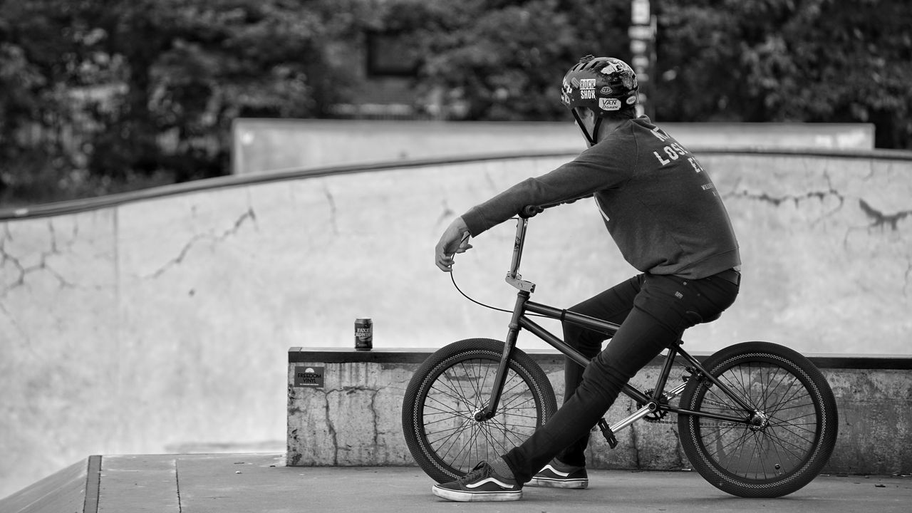 bicycle, real people, full length, leisure activity, one person, outdoors, day, transportation, cycling, riding, focus on foreground, mode of transport, men, sport, lifestyles, casual clothing, land vehicle, helmet, skateboard park, stunt, skill, young adult, headwear, cycling helmet, people