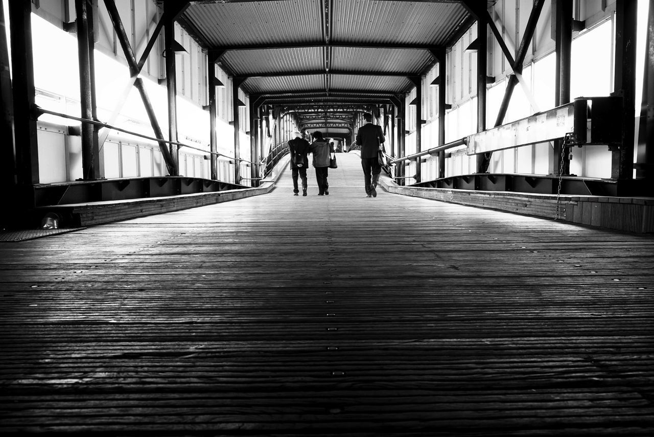 Rear View Of People Walking On Bridge