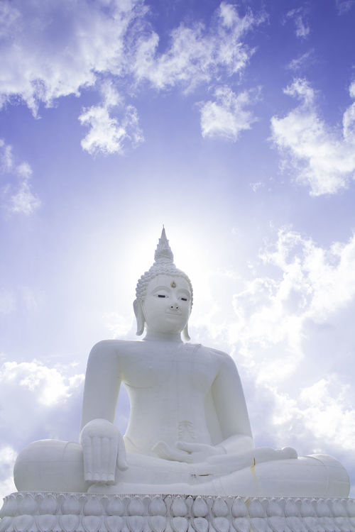 White Buddha with daytime sun, wear a beautiful Day Human Representation Idol Low Angle View Male Likeness No People Outdoors Religion Sculpture Sky Spirituality Statue Chum Phae,khonkaen,Thailand