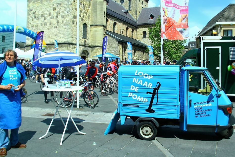 Go and/or Fetch Me Some Water Architecture Blue Built Structure Car Taking Over City City Life Cycle Race Day Good Cause Gotohell Heerlen Land Vehicle Men Mode Of Transport Motor Scooter Outdoors People And Places Person Sitting Street Transportation Water For Ghana CyclingUnites The Drive