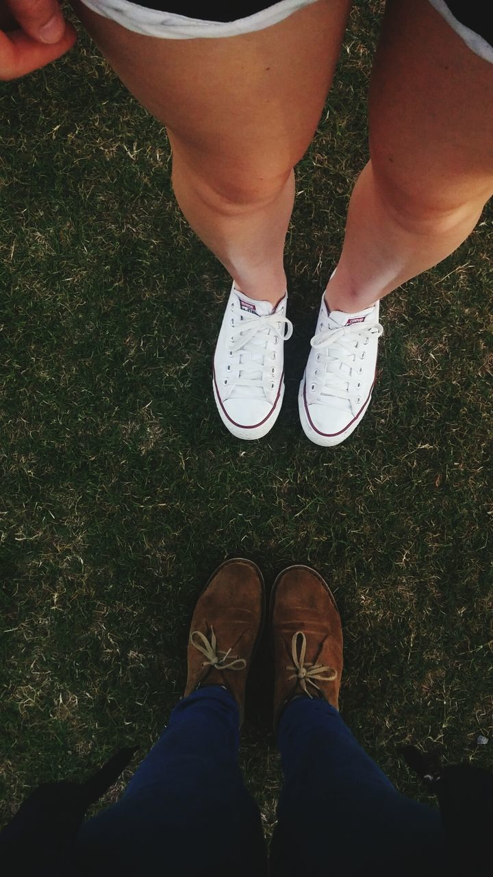 Low Section Of Man And Woman Wearing Shoes Standing In Lawn